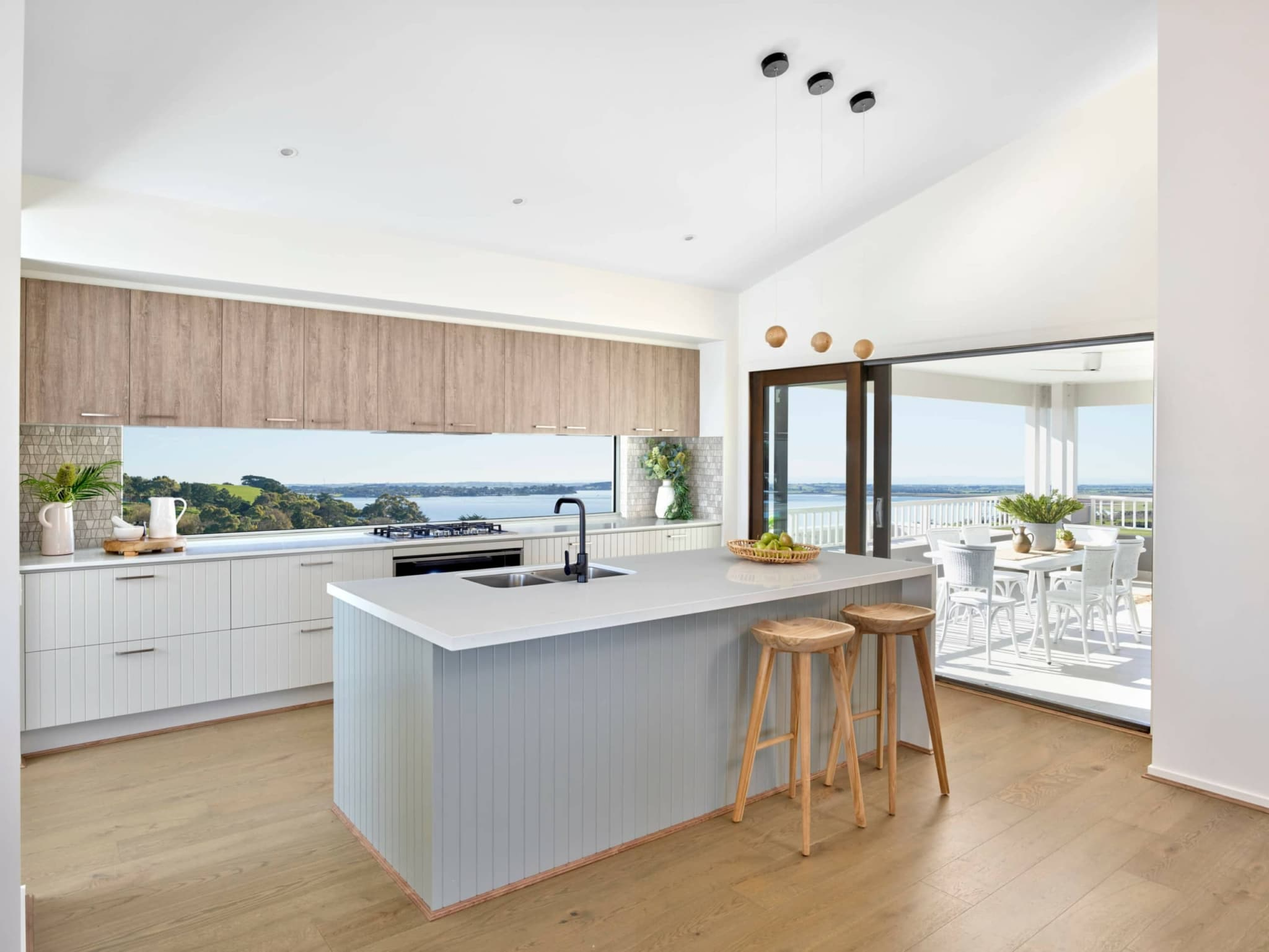 metricon coastal kitchen with vj panel cabinets and glass window splashback