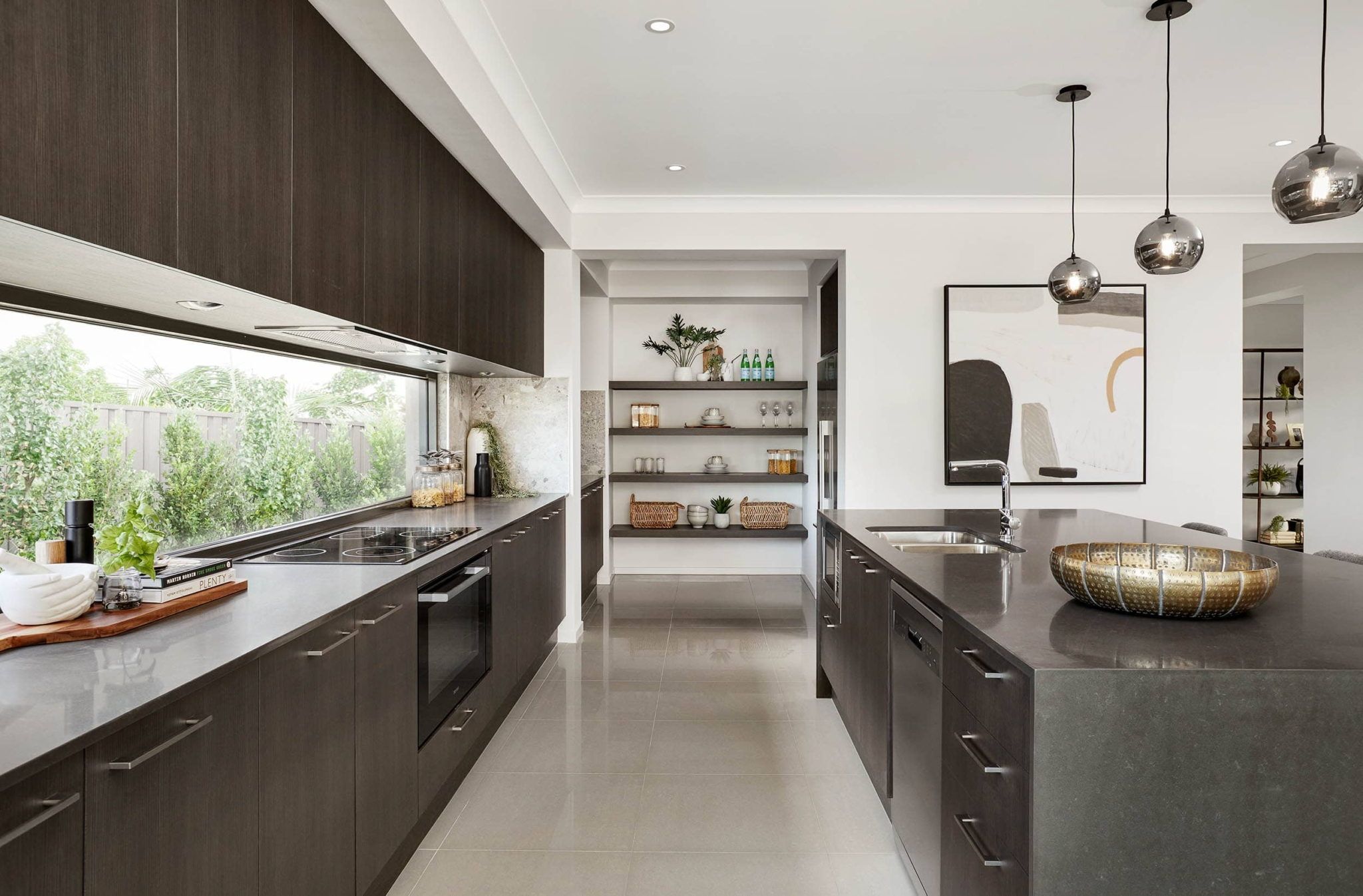 metricon kitchen with dark brown cabinets and blackmarble benchtops with butlers pantry
