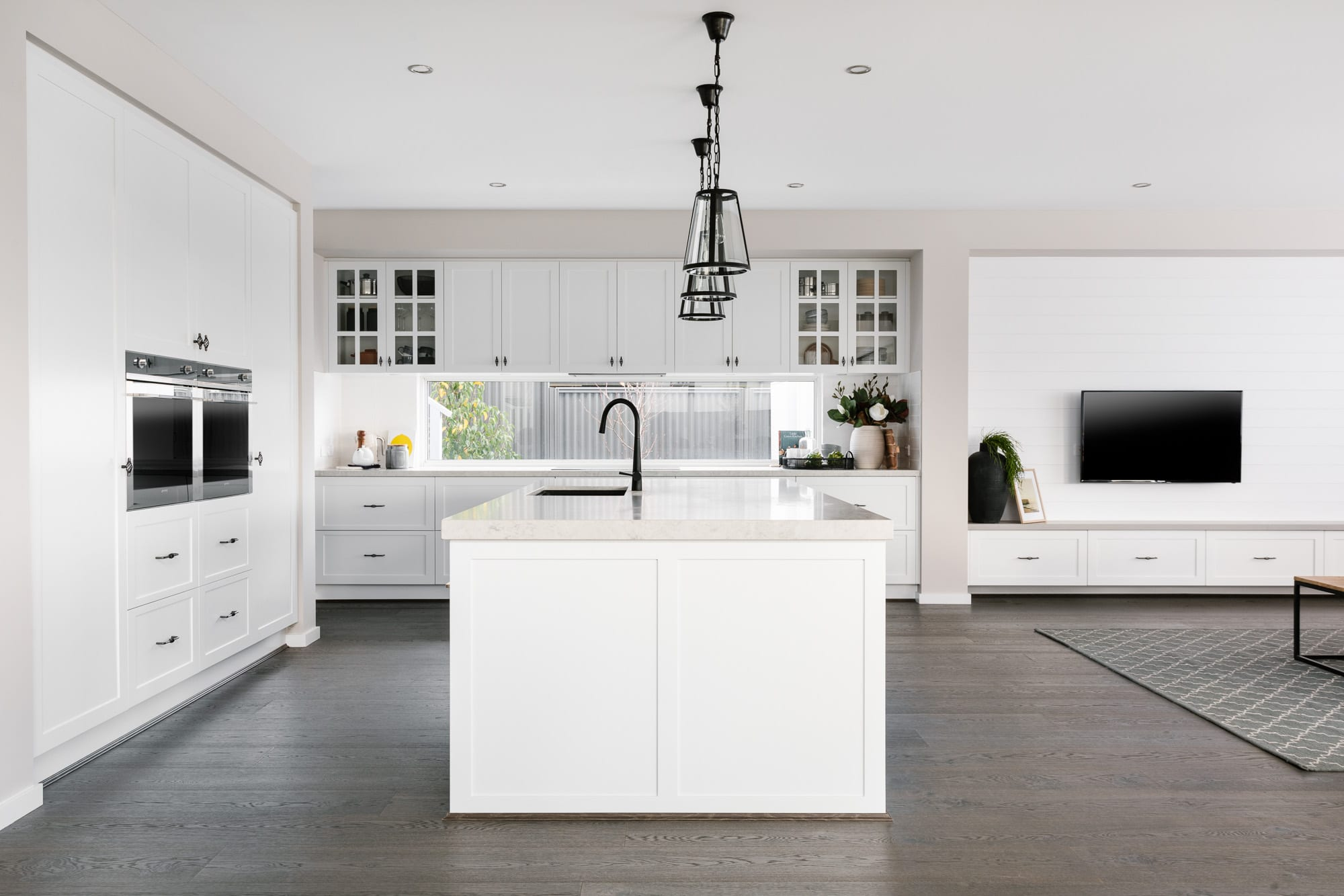 metricon white shaker kitchen cabinets with black metal handles and industrial pendant lights over island