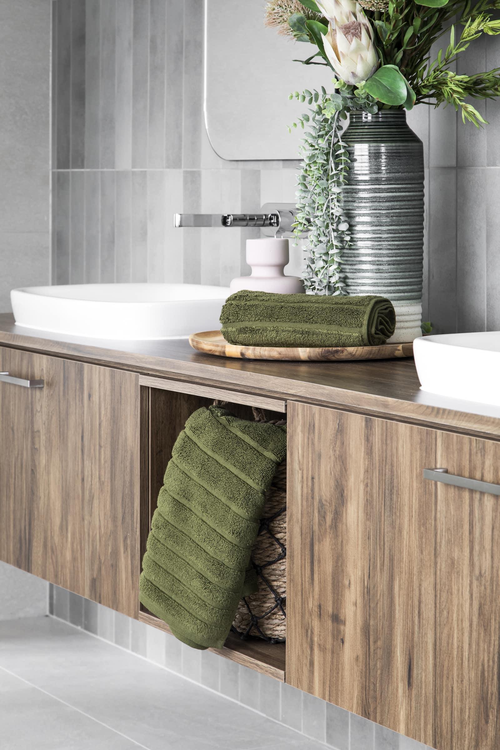 brown timber floating bathroom vanity with green towels