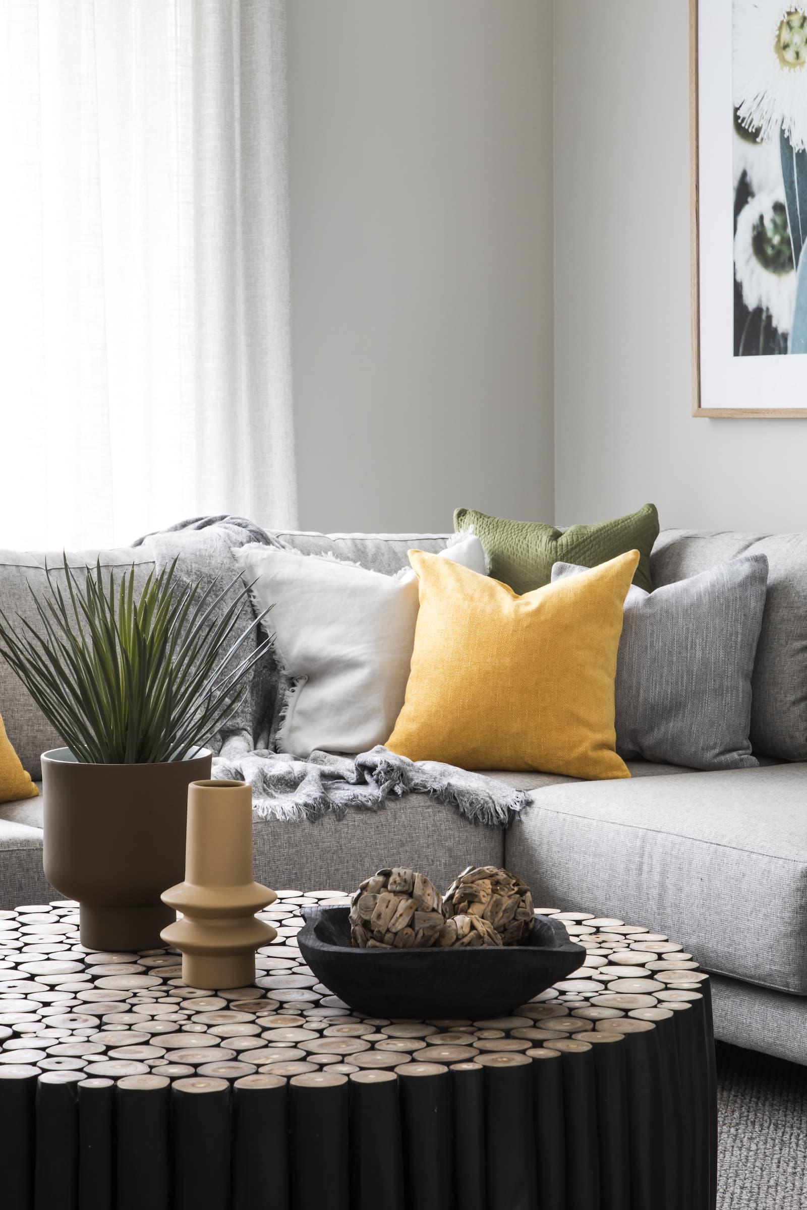 green and yellow cushions on grey sectional sofa with round black log coffee table