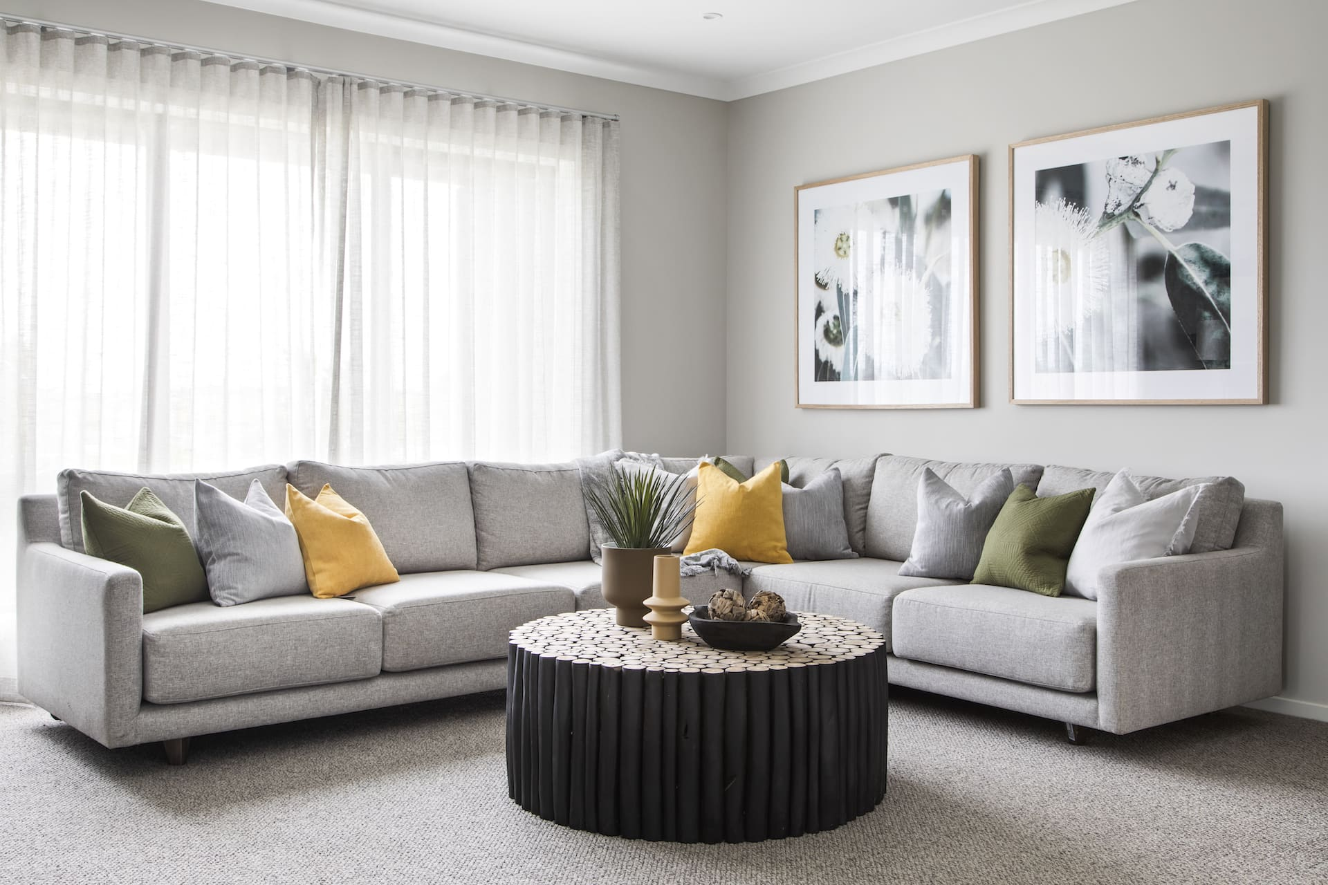 grey sectional sofa with round black timber table and green and yellow cushions