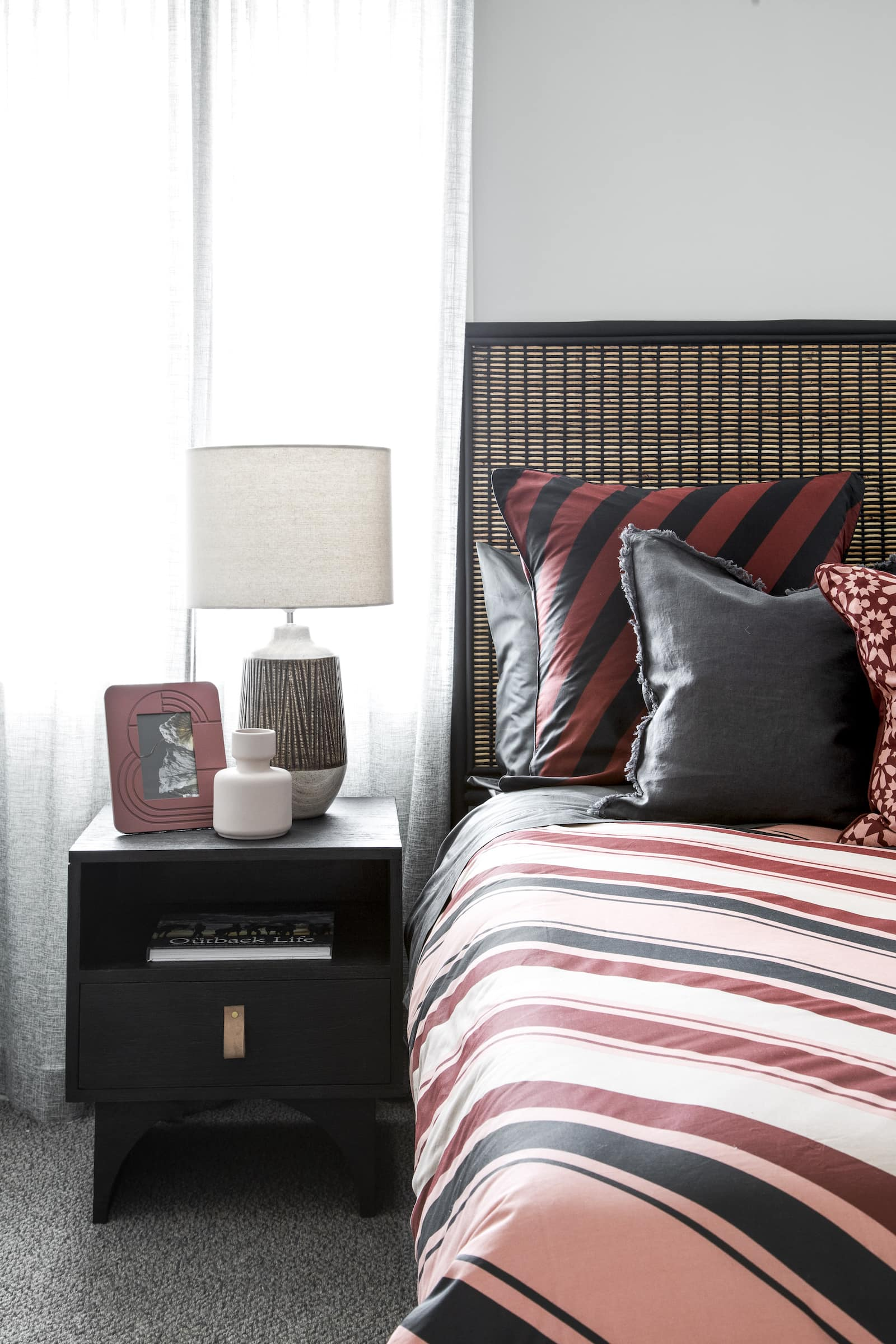 lorraine lea red and black stripe bedding in bedroom with black timber bedside tables