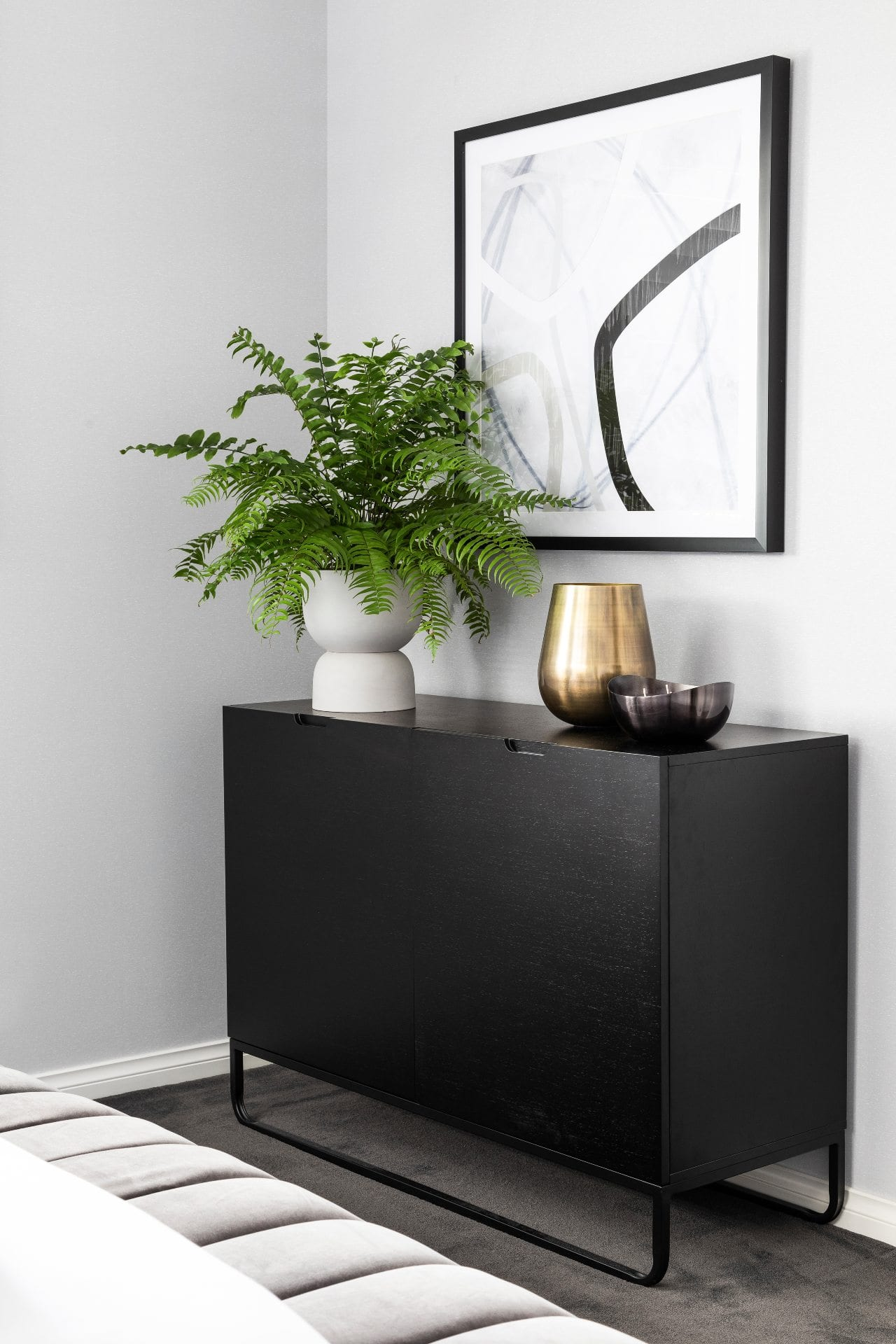 black sideboard with metal legs boston fern indoor plant and black and white abstract art in bedroom