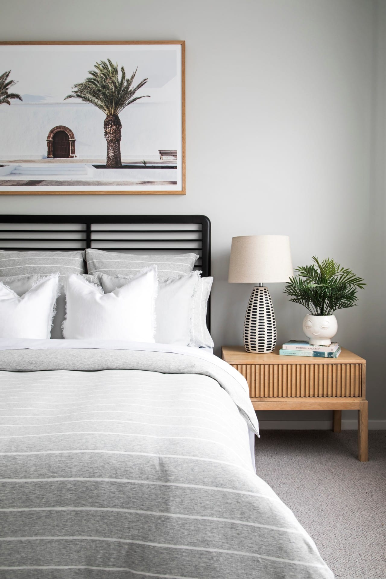coastal bedroom with grey and white stripe bedding black timber slat headboard and palm tree art