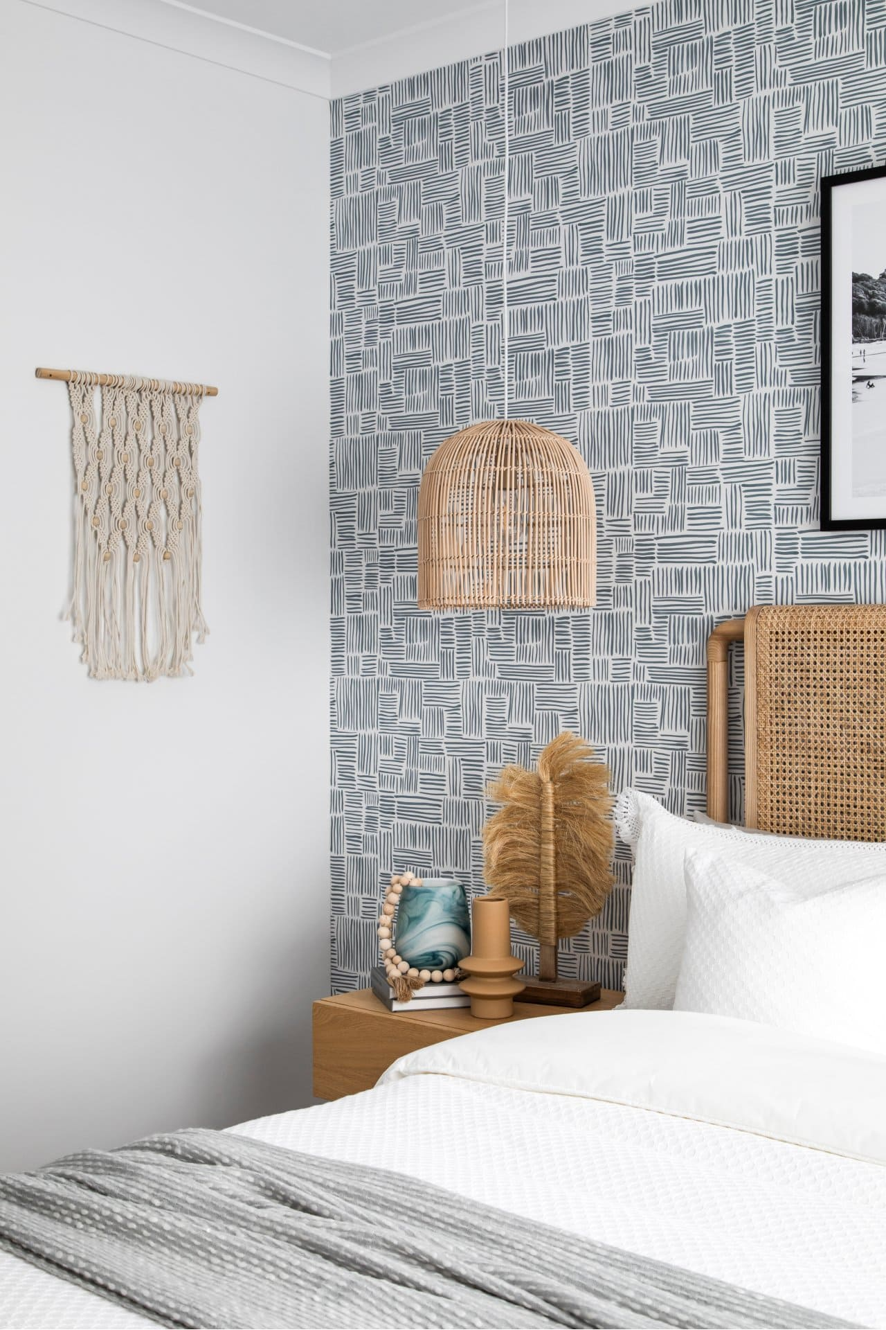 coastal bedroom with macrame wall hanging and blue and white wallpaper design rattan pendant light