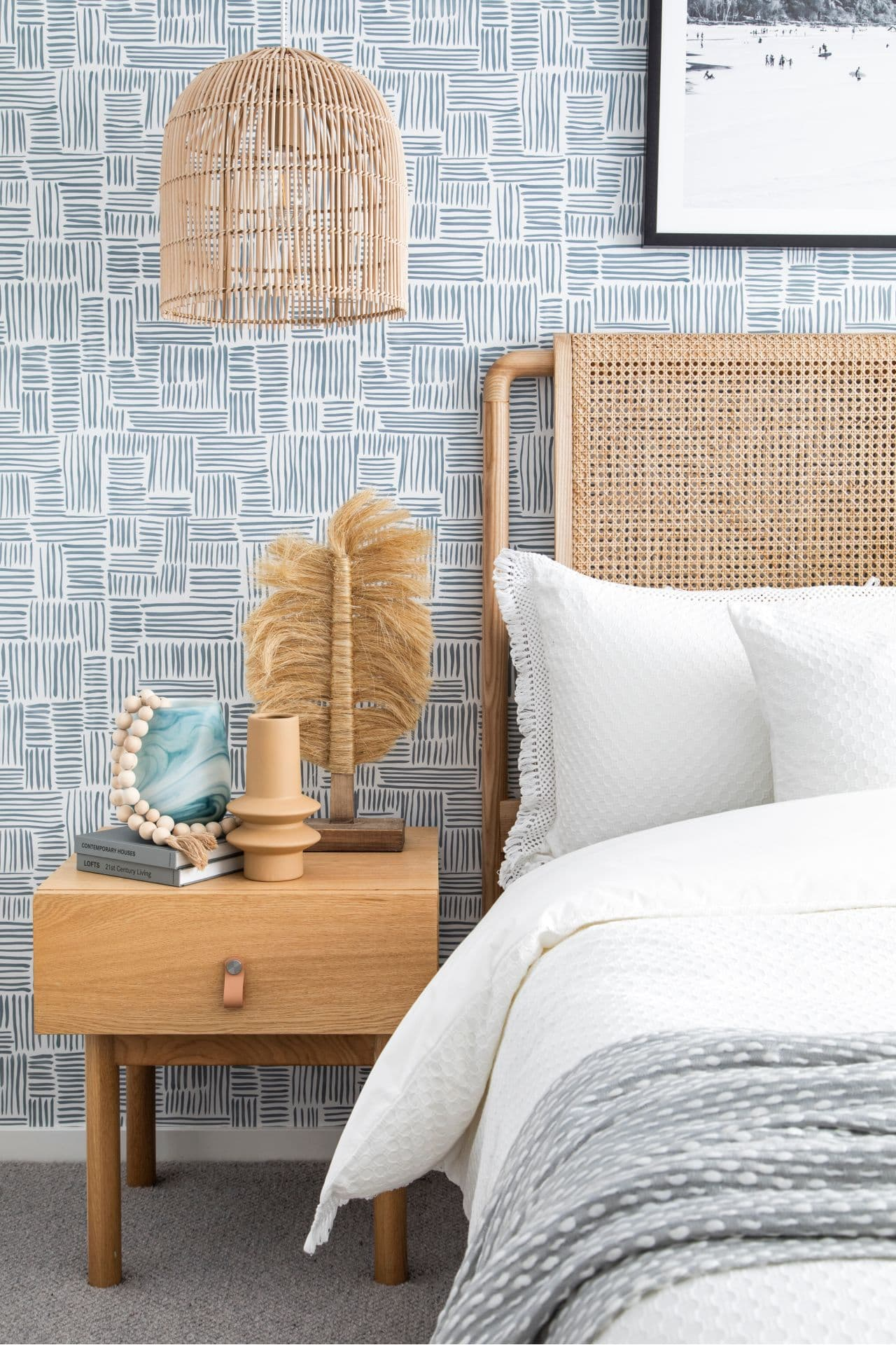 coastal bedroom with rattan headboard and pendant light and white bedding with grey throw