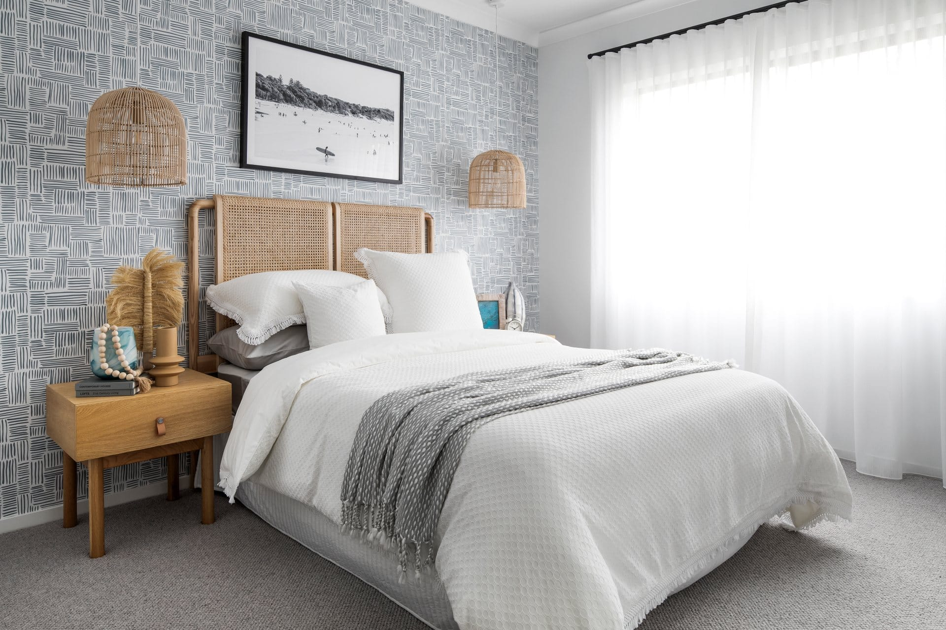 coastal bedroom with white bedding rattan pendant lights and blue wallpaper design