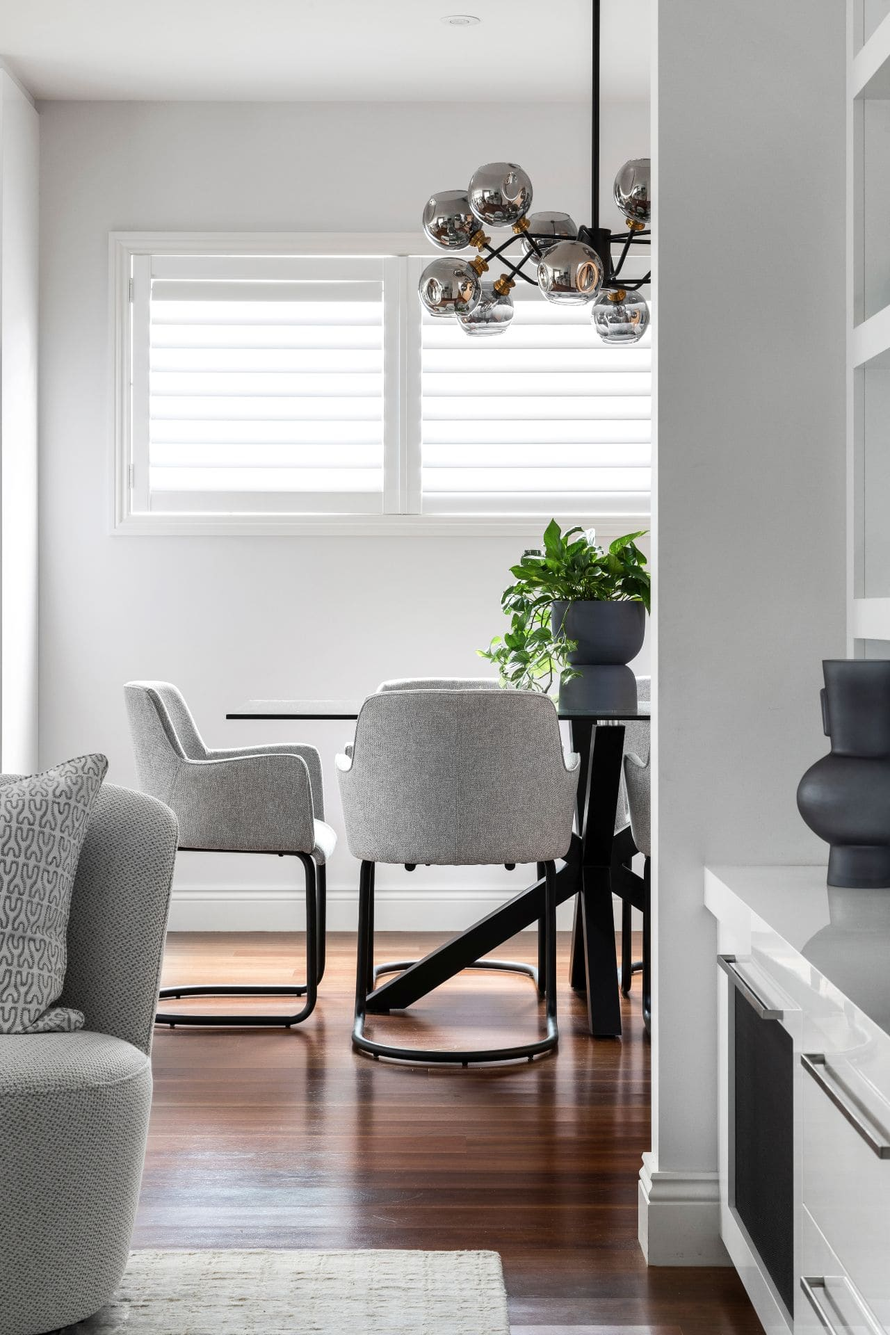 dining room with grey upholstered chair glass dining table and plantation shutters