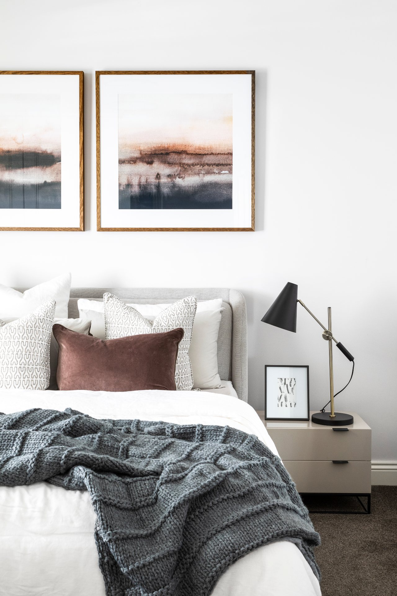 masculine bedroom design with mid century bedside table lamp grey throw and brown velvet cushion on bed