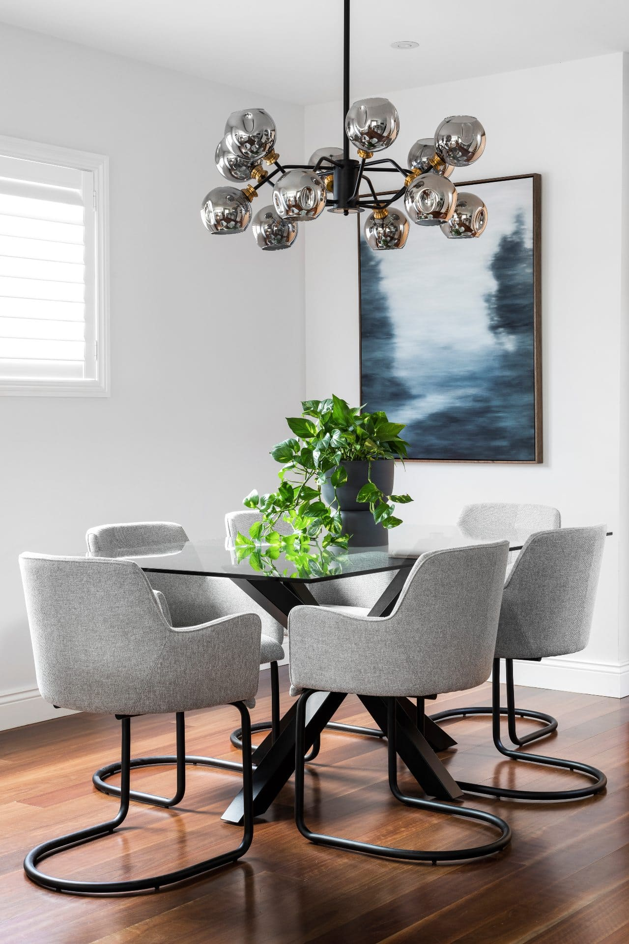 modern dining room design with glass rectangle dining table grey upholstered chairs and mid century glass pendant light
