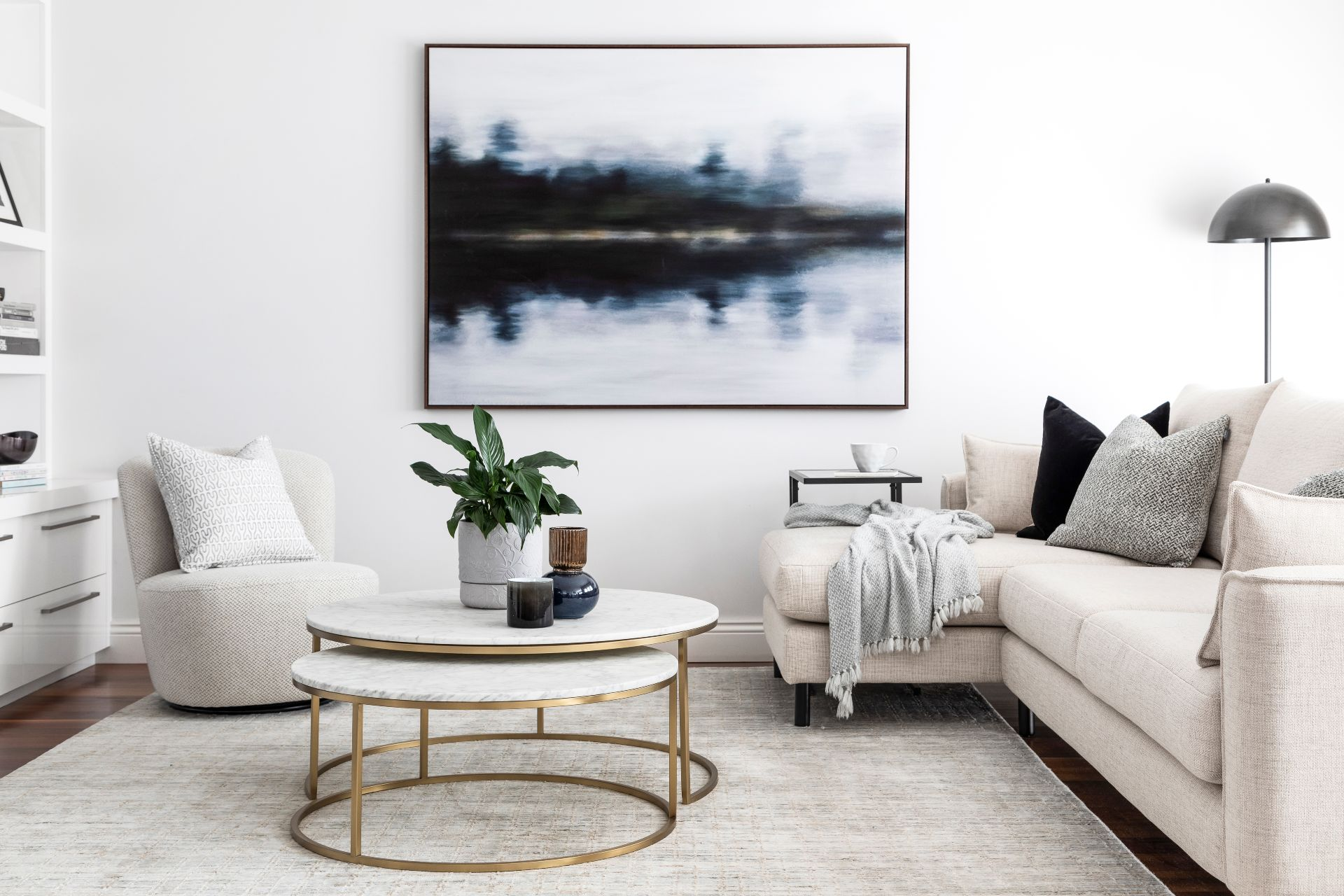 monochromatic living room with moody abstract art from urban road and round marble coffee table