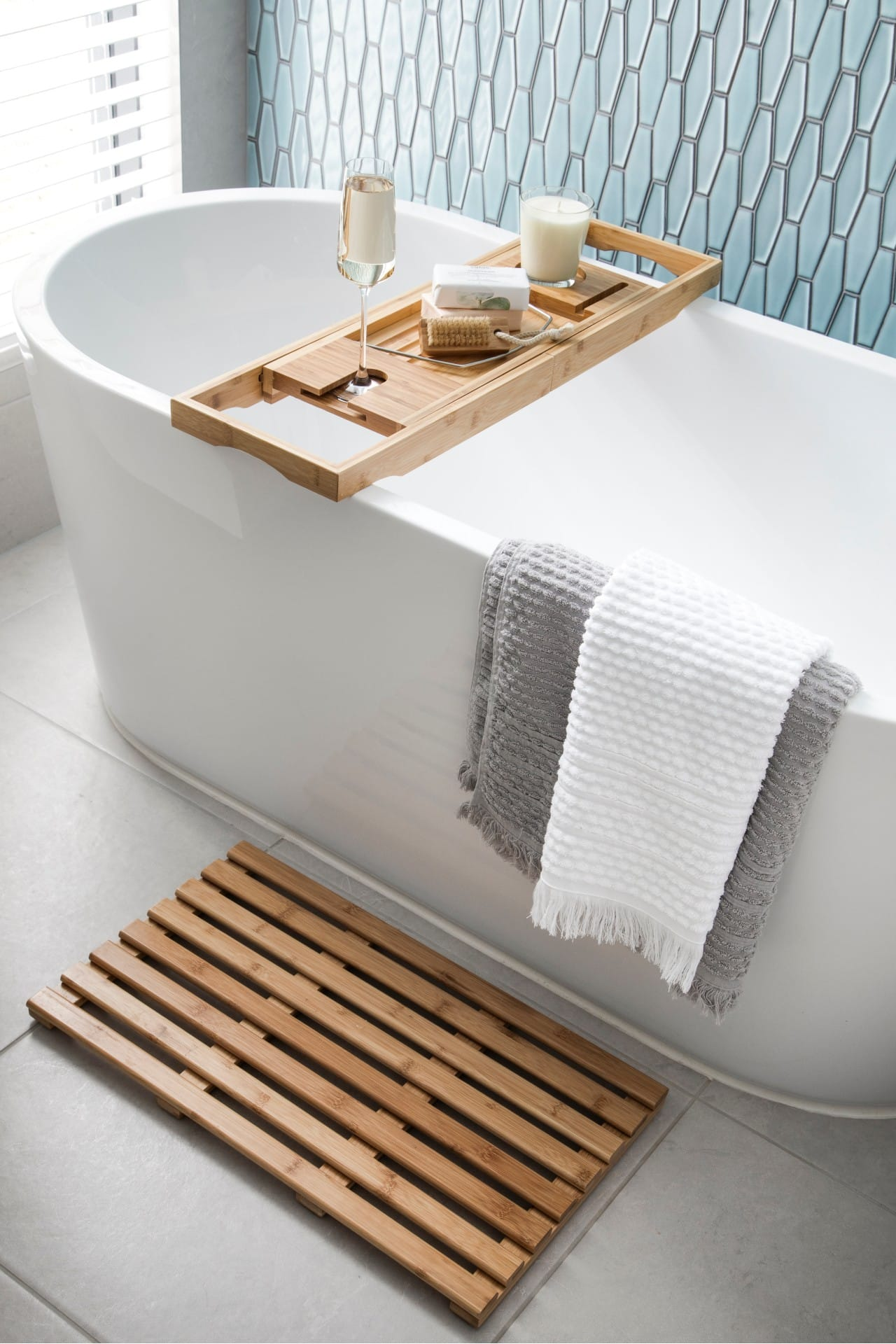 white freestanding bath tub with bamboo bath caddy and floor mat grey and white fringe bath towels
