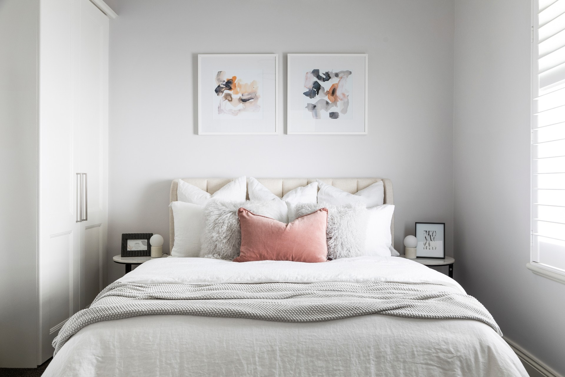 white guest bedroom with beige upholstered bed frame mongolian cushions and blush velvet cushion