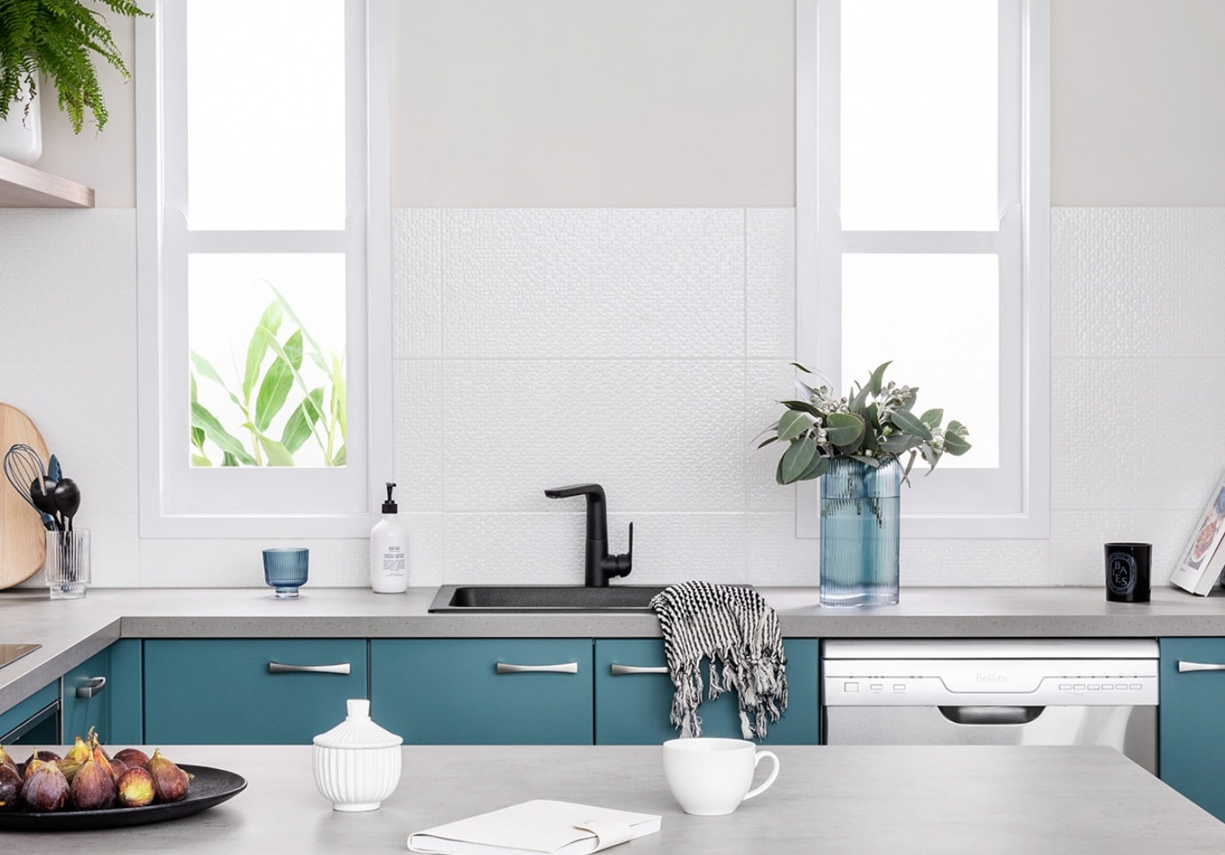 dark teal kitchen cabinets with black sink grey countertop and white walls