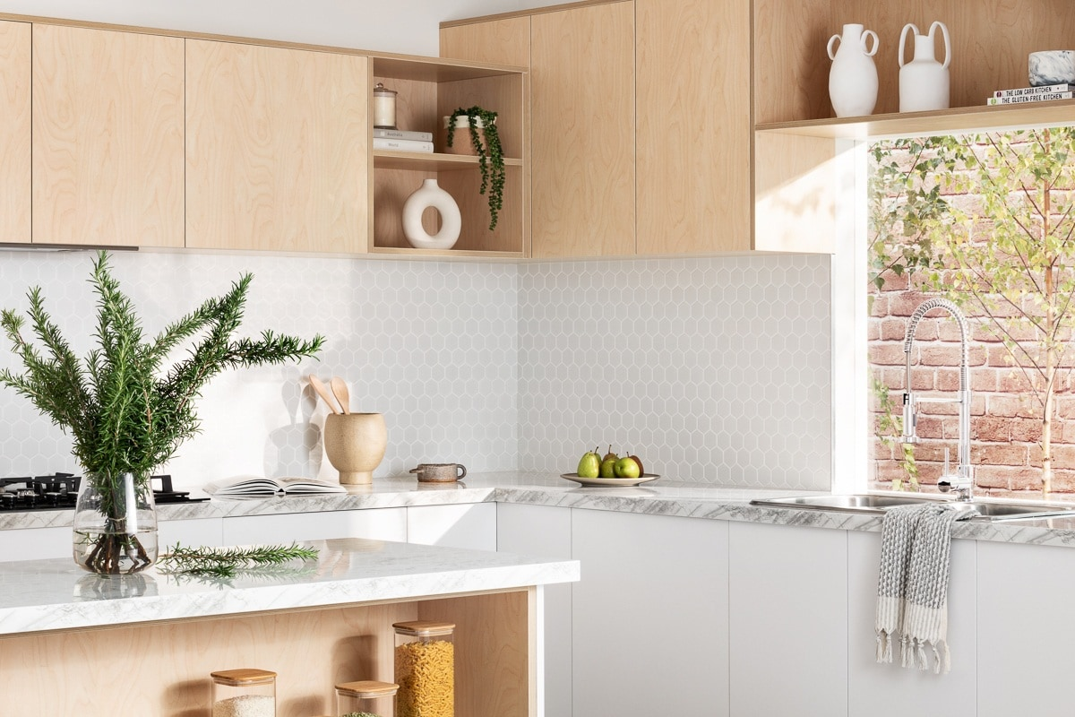 plywood kitchen from kaboodle kitchens with white marble countertops and white hexagon tile splashback