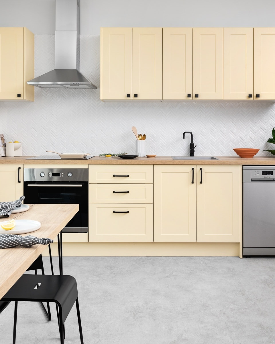 yellow kitchen cabinets with timber benchtop black handles and grey concrete floor