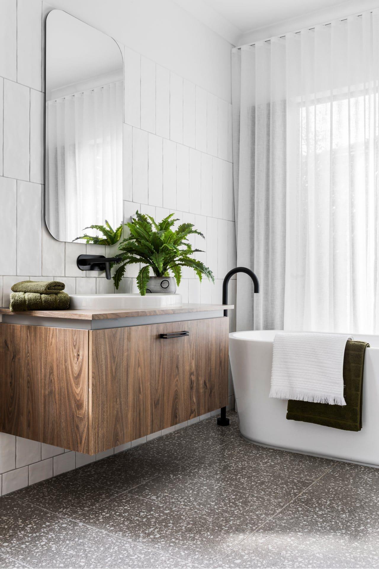bathroom with grey terrazzo floor tile floating timber vanity black tapware sheer curtains