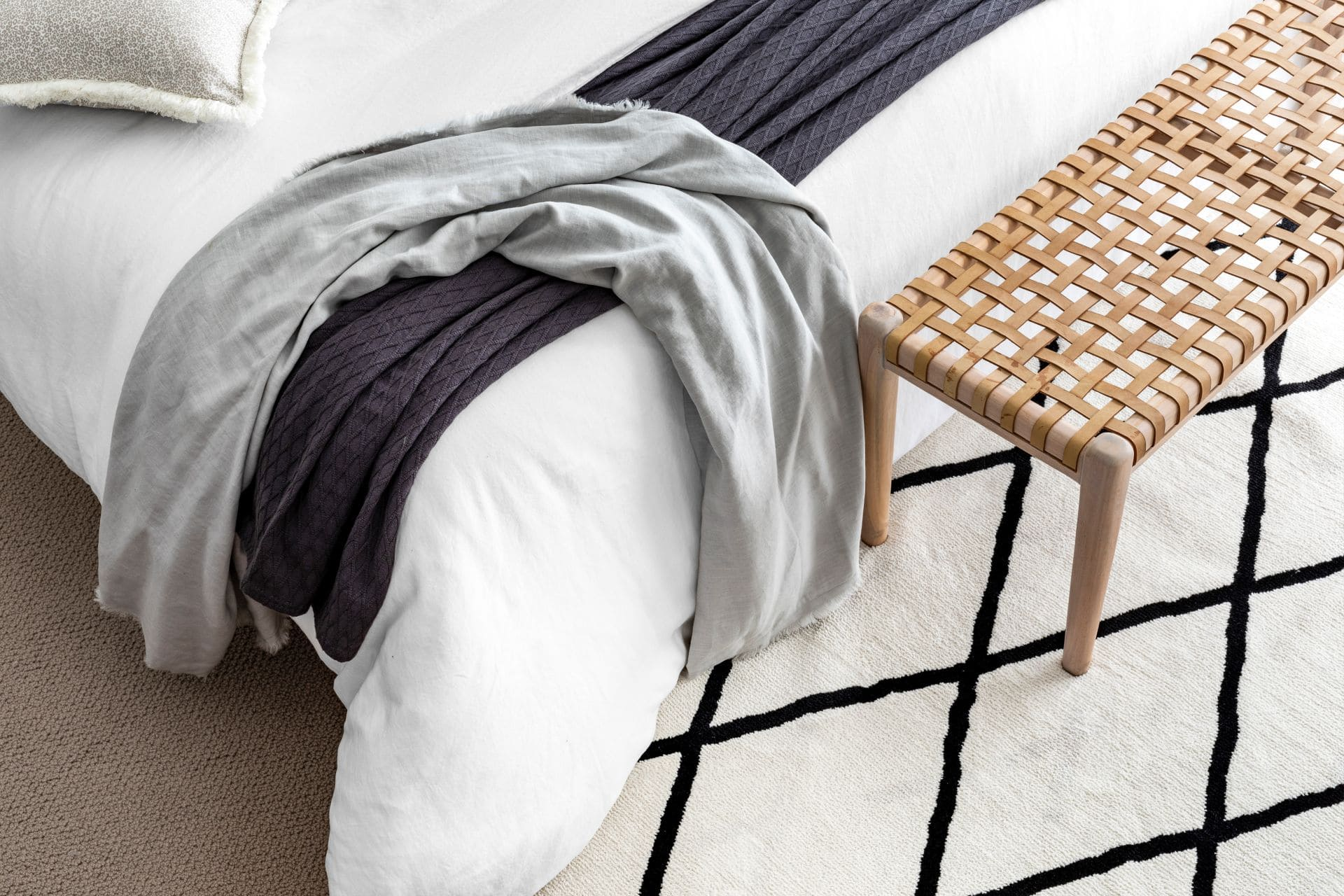 diamond floor rug in bedroom with woven leather bench seat at end of bed
