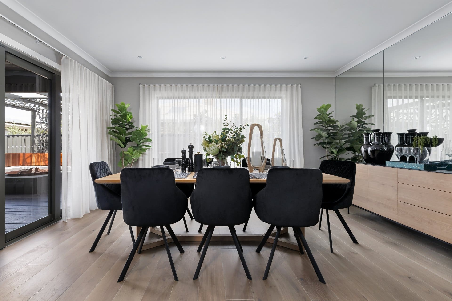 dining room with black fabric chairs and white sheer curtains with s fld heading