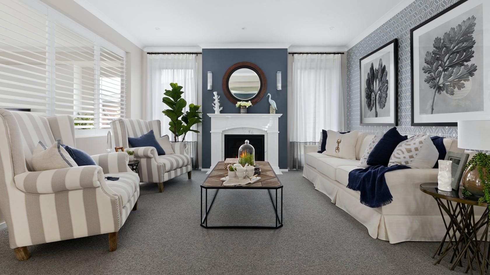 formal hamptons living room with striped grey and white armchairs and fireplace with mirror above
