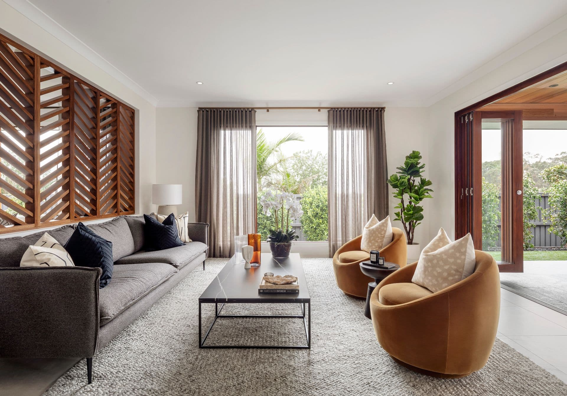 formal living room design with large window and orange velvet armchairs across from dark grey sofa