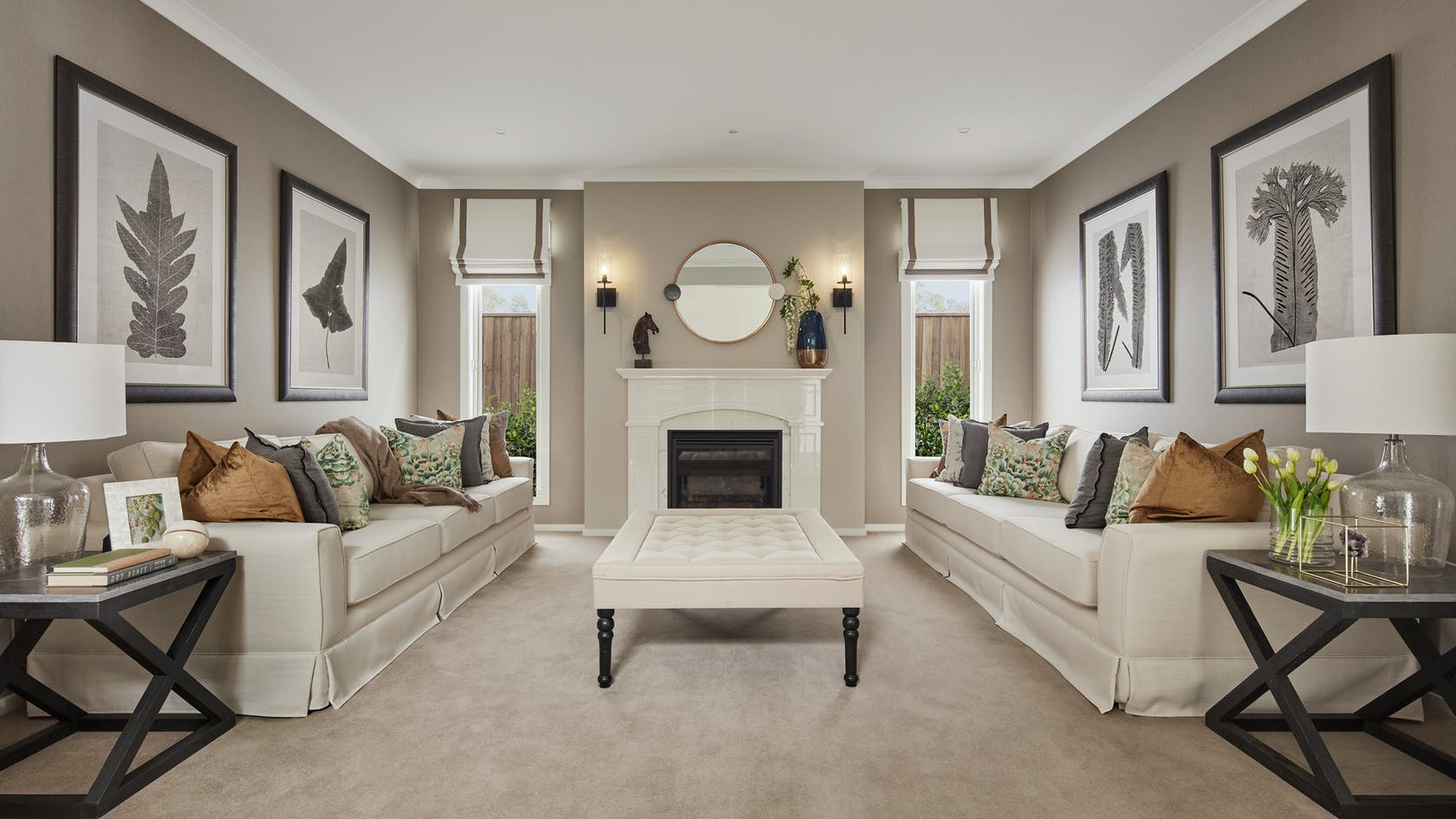 formal living room styled with provincial furniture and fireplace with round mirror above