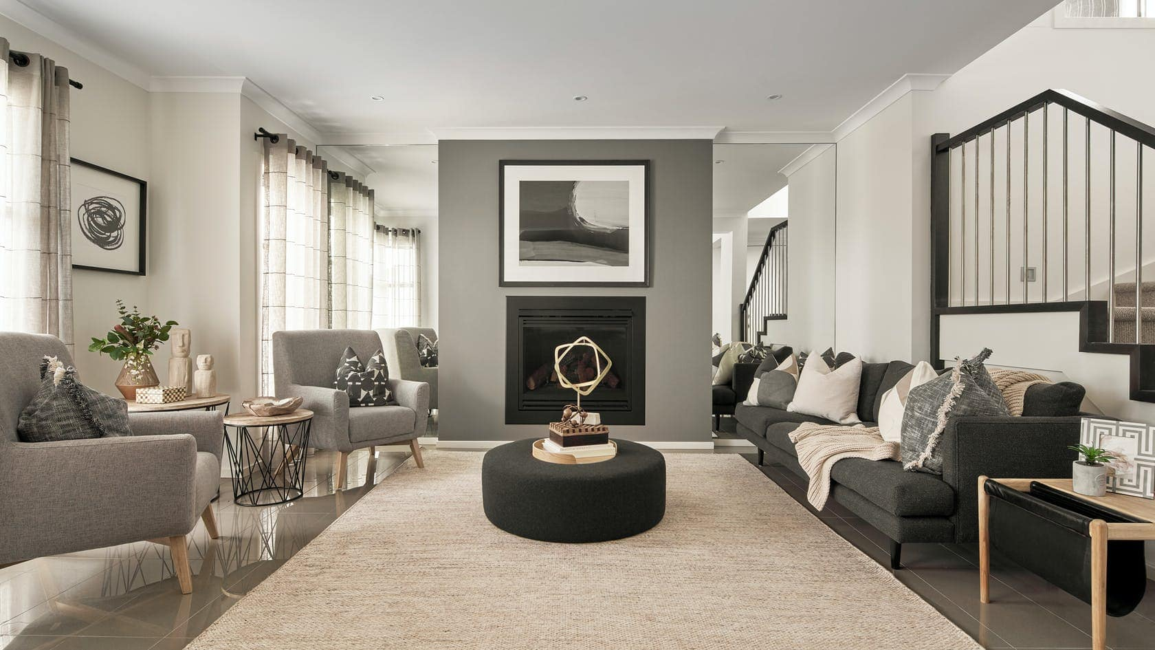 formal living room styling with black and grey furniture and fireplace with art above furniture