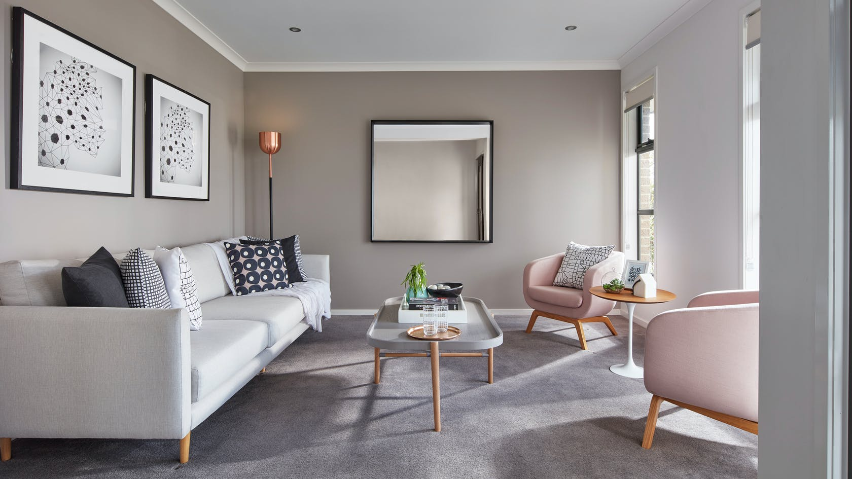 formal living room styling with mirror on wall pink armchairs and grey sofa