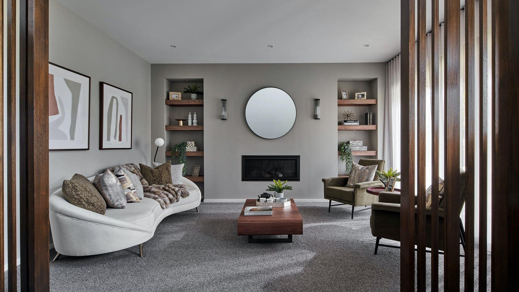 formal living room with curved sofa grey walls and fireplace with round mirror above