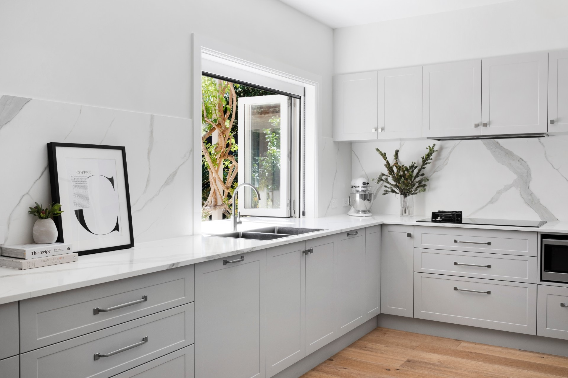 grey and white shaker style hamptons kitchen with oak flooring white stone splashback and servery window