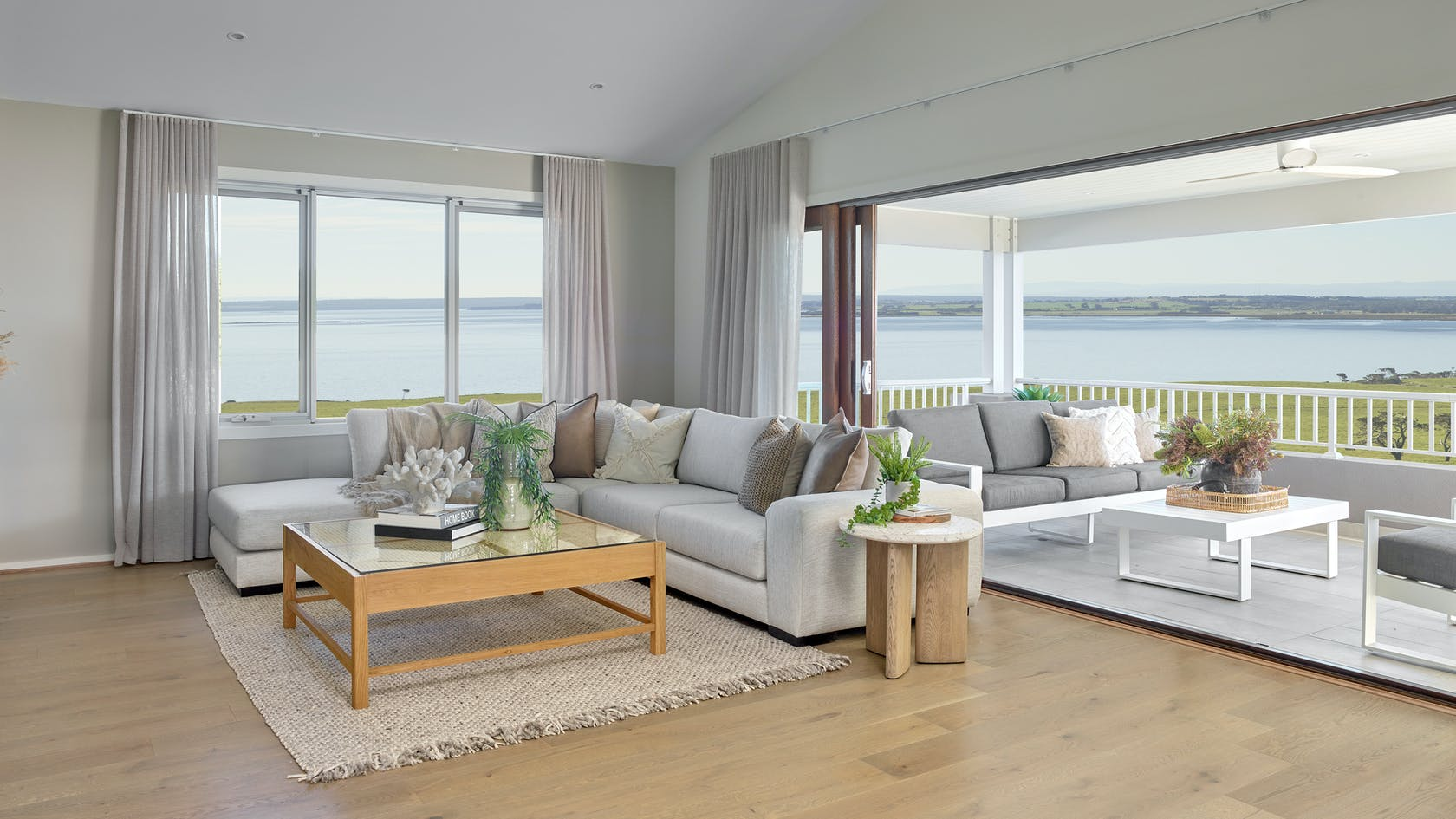 light grey sheer curtains in coastal living room with high ceiling