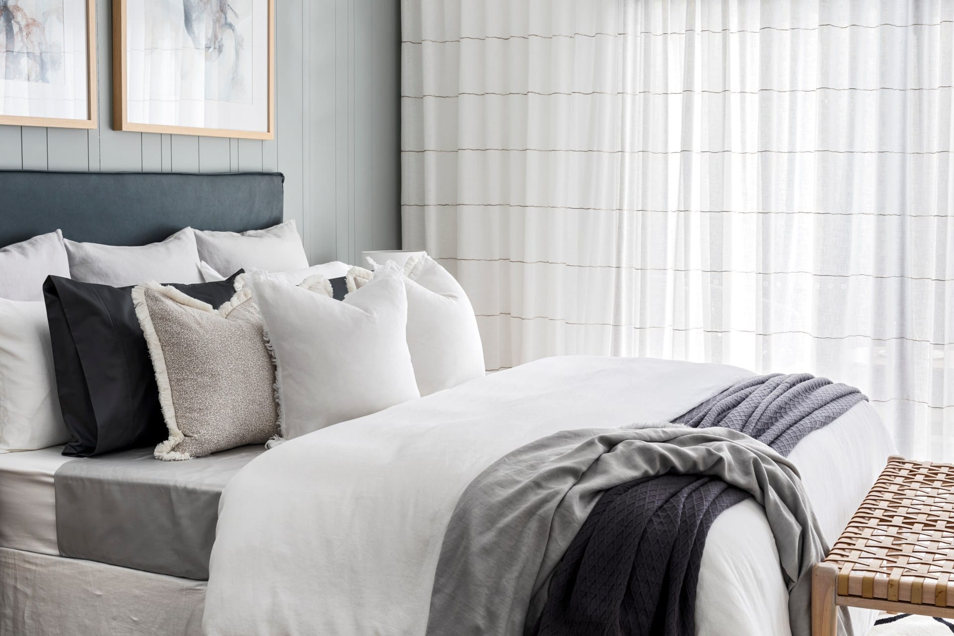 neutral bed styling with lots of pillows in bedroom with sheer curtains
