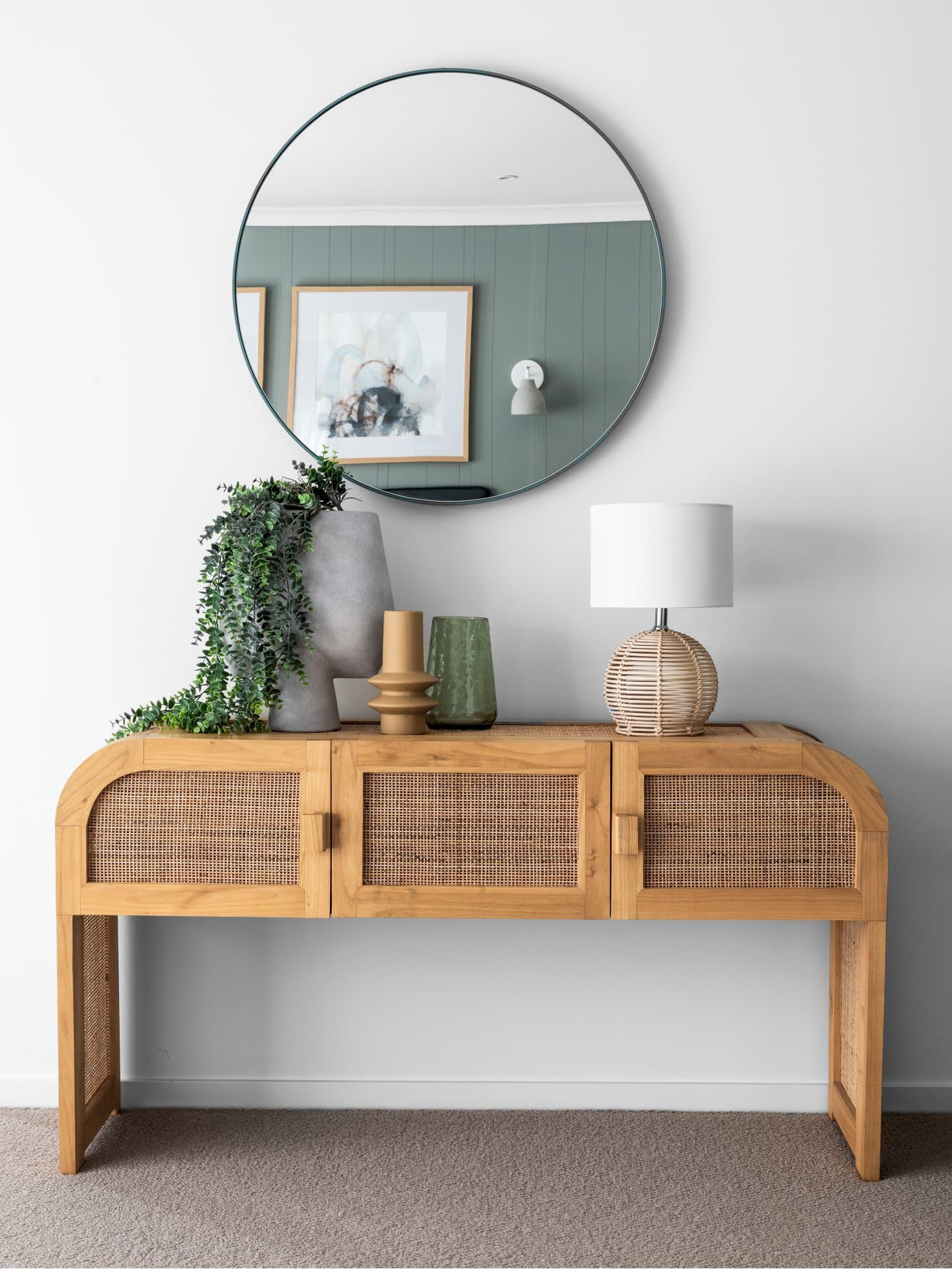 rattan curved console table with round mirror above styled with coastal table lamp and concrete vase