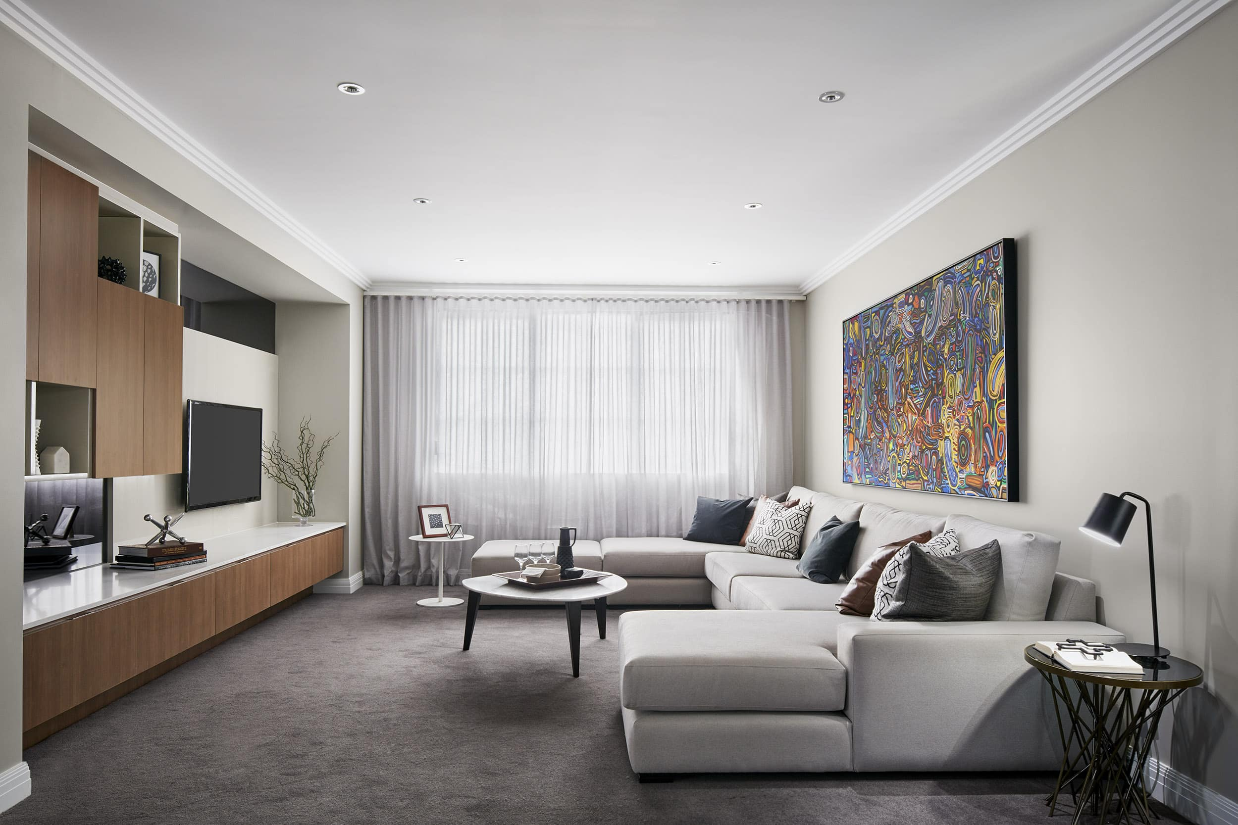 rumpus room with large sectional sofa and media cabinetry with mounted tv