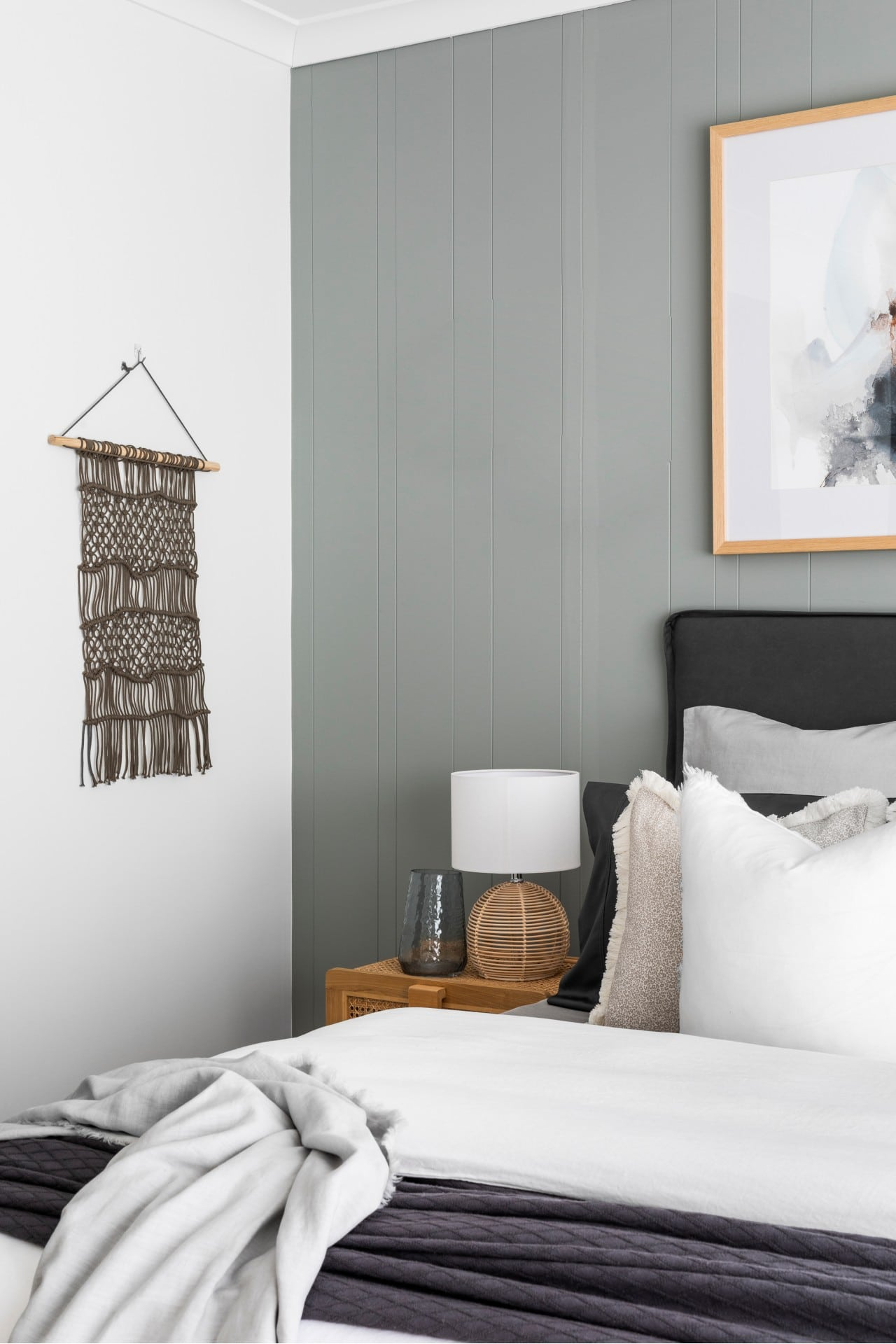 sage green vj panel bedroom with white bedding and macrame wall hanging