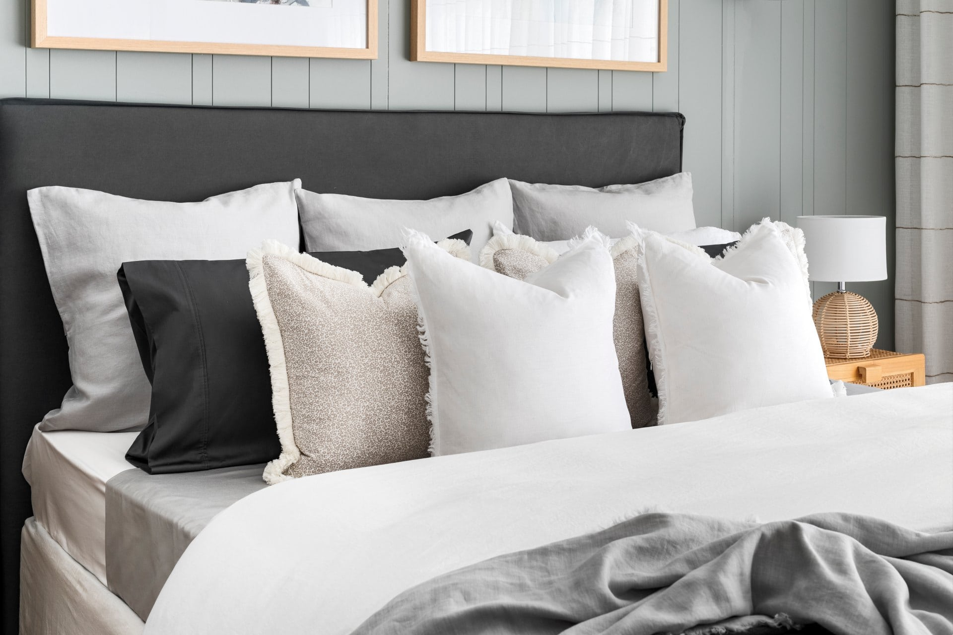 styling a bed with pillows and cushions white bedding grey headboard sage green vj panel wall