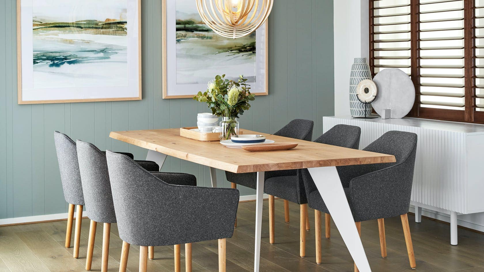 oak dining table with white metal legs in dining room with sage green feature wall
