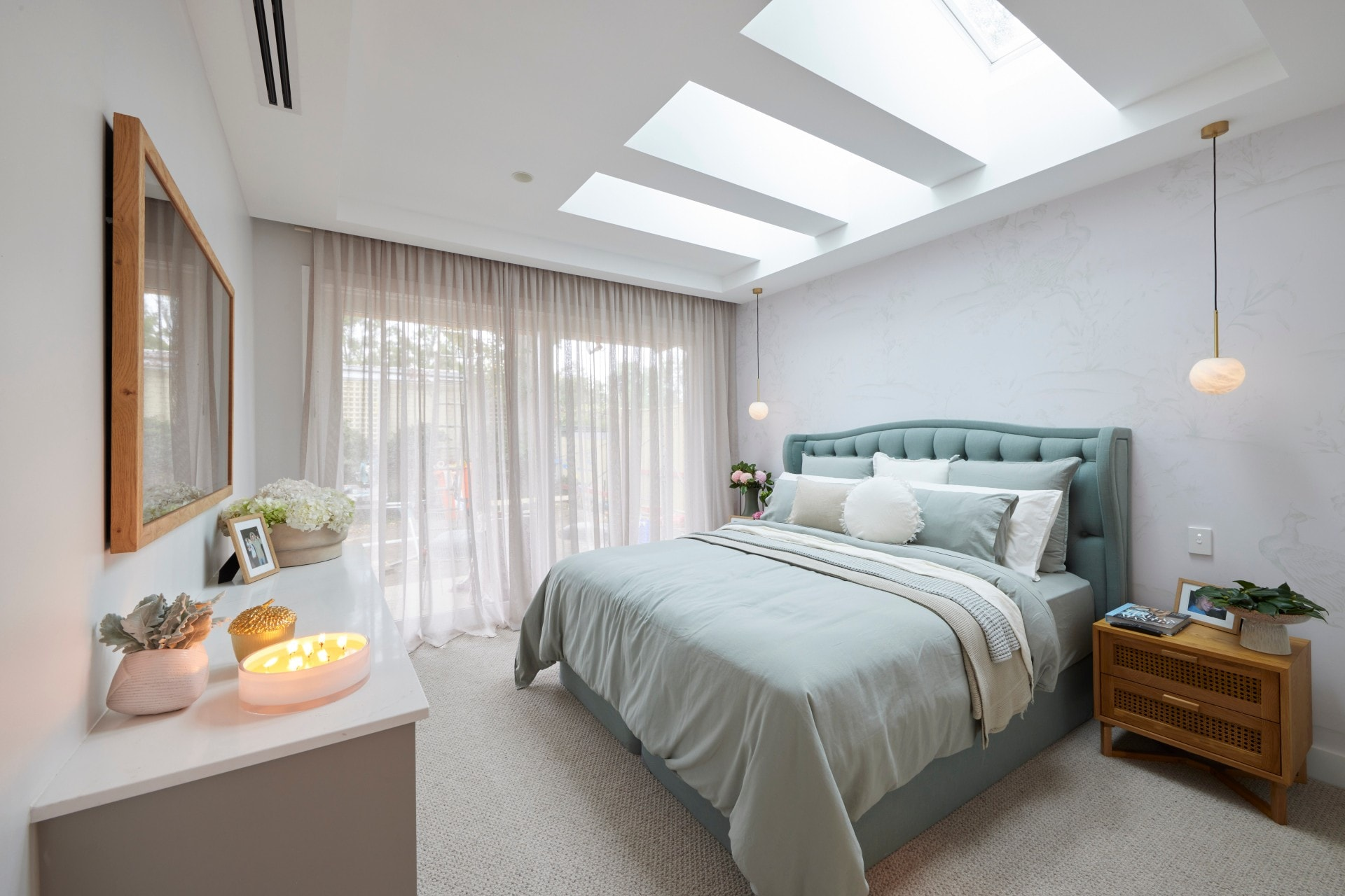the block 2021 mitch and mark master bedroom with teal upholstered bed frame and skylights