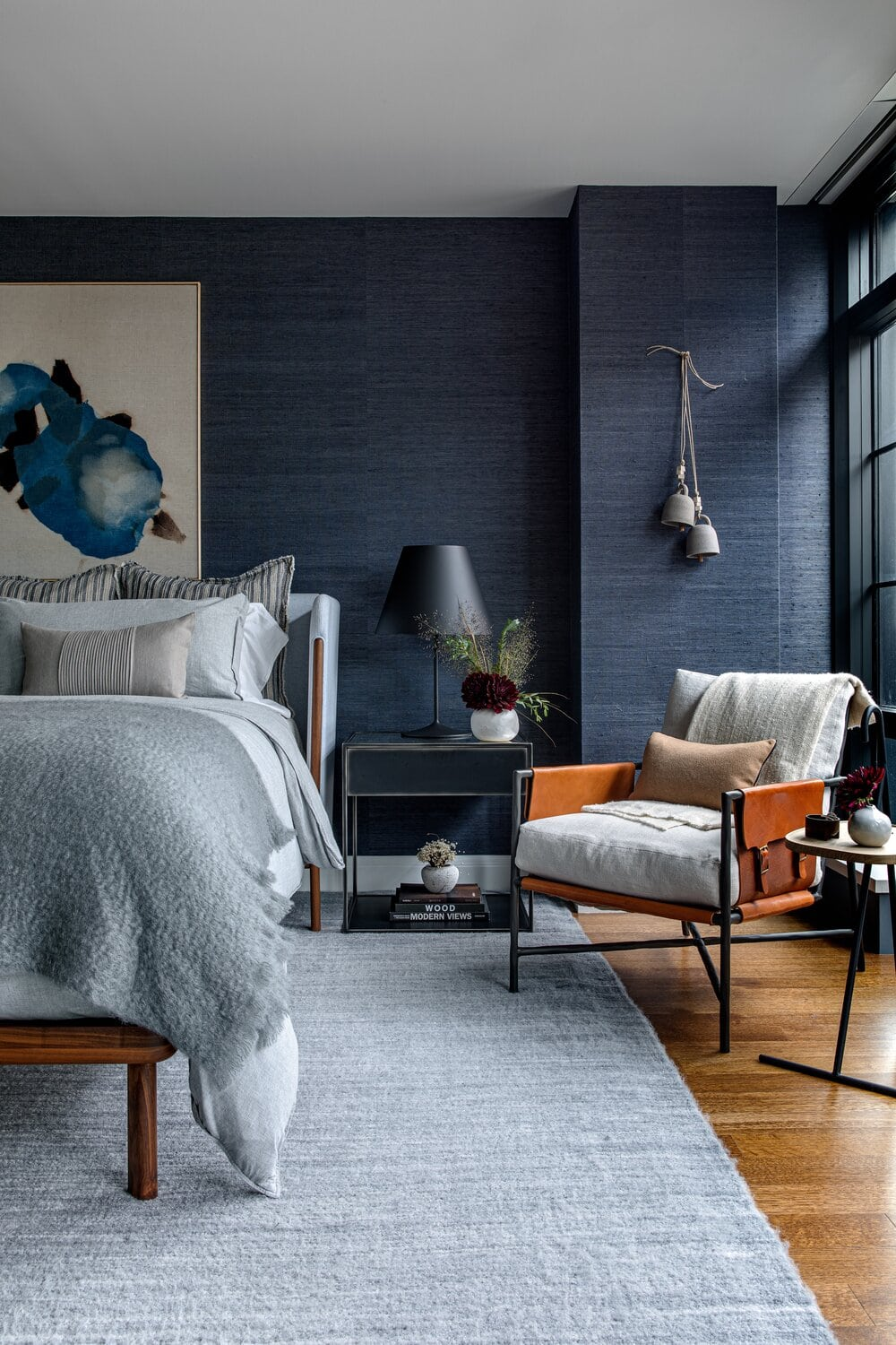 bedroom with large grey rug and blue cloth wallpaper