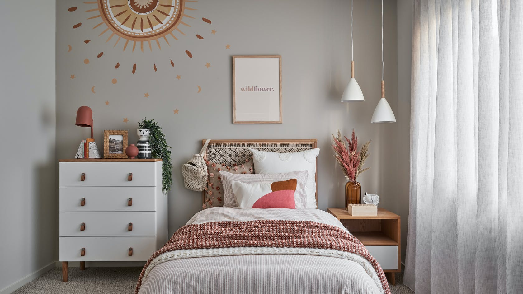 bohemian little girls bedroom with rattan headboard and white sheer curtains