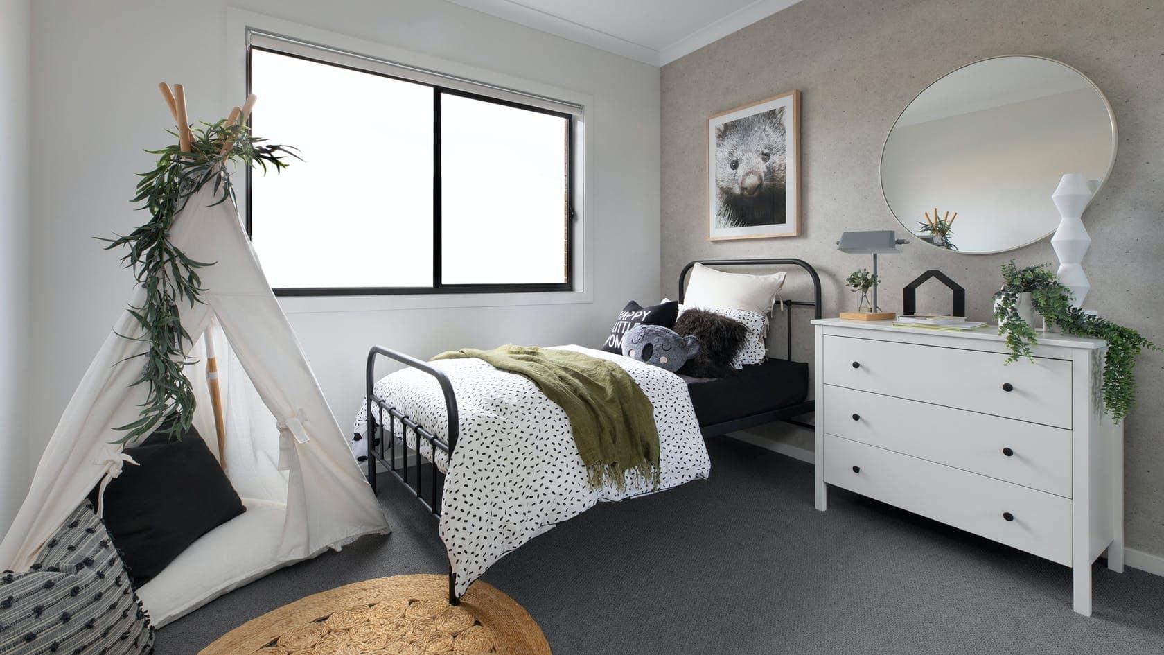 single black metal bed frame styled in kids bedroom with koala cushion