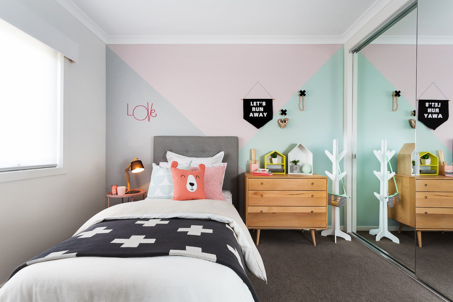 single grey fabric bed styled in kids room with pink and sage painted walls
