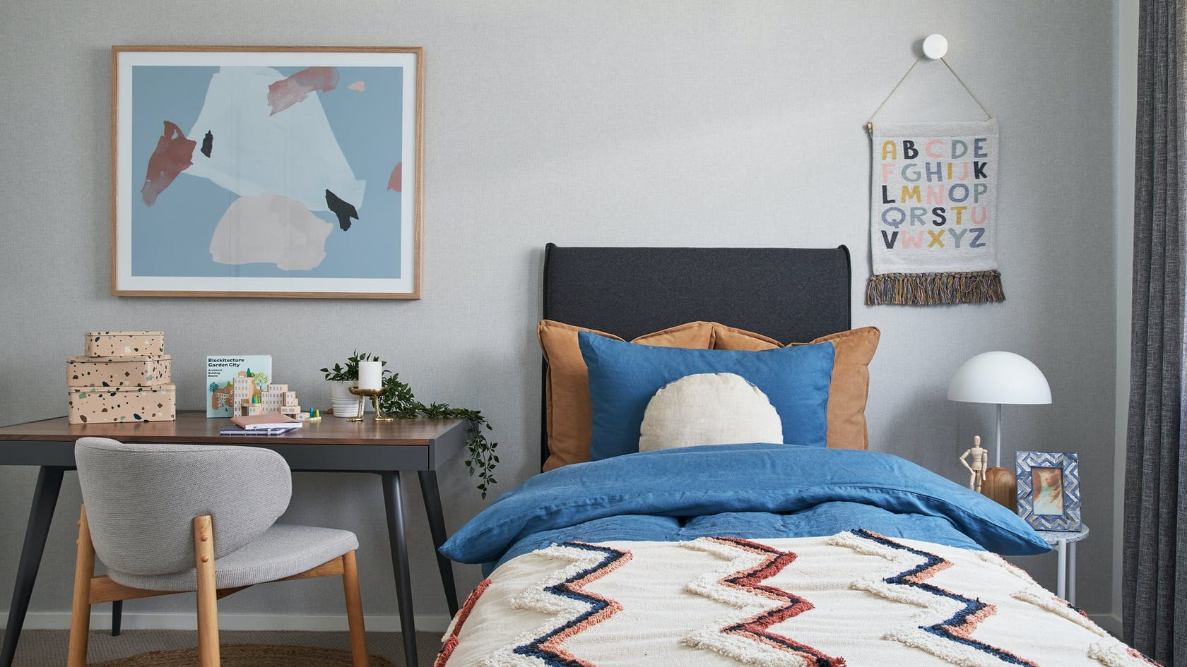 single grey upholstered bed frame styled with patterned kids quilt cover set