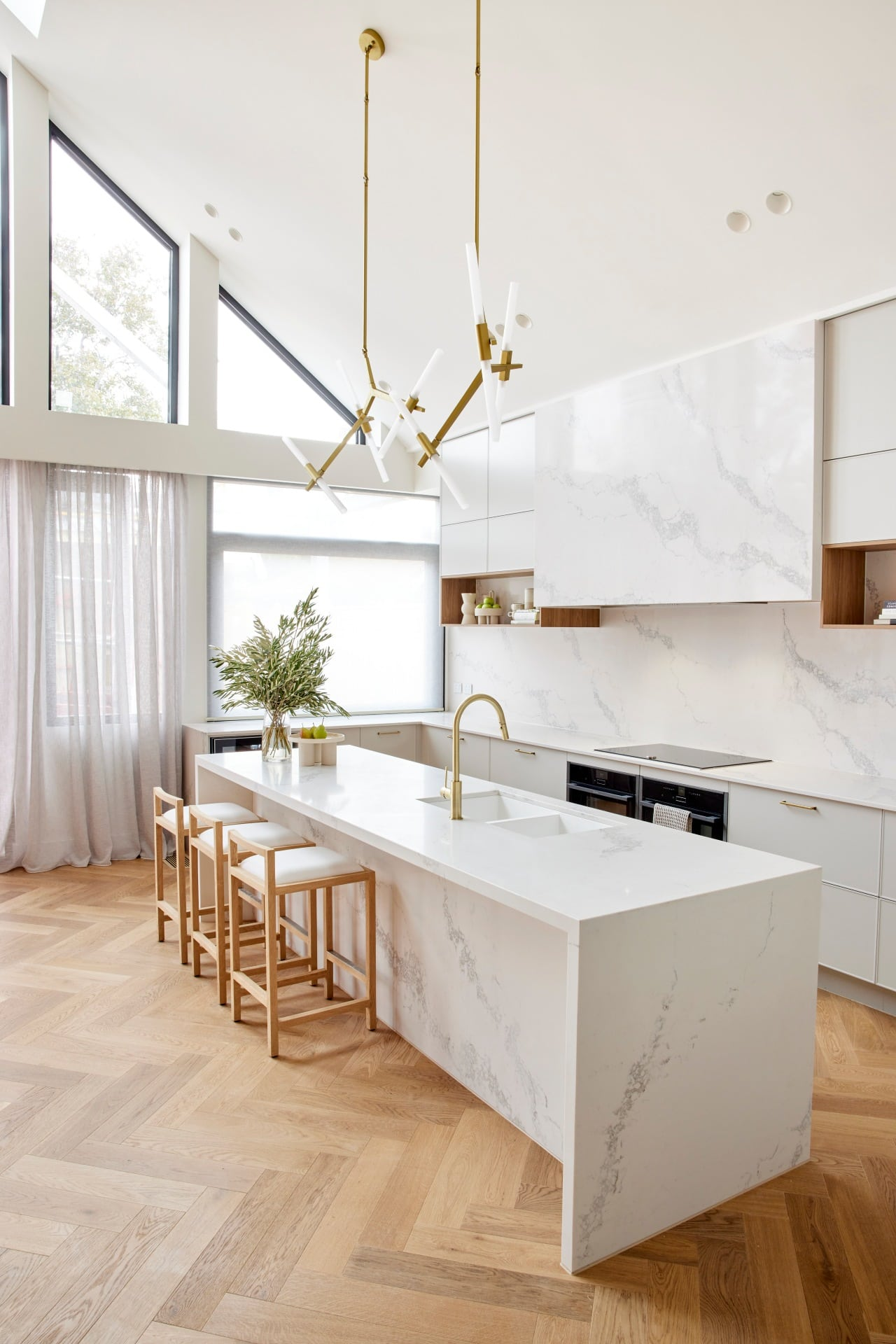 the block 2021 ronnie and georgia kitchen with brass pendant lights above marble kitchen island