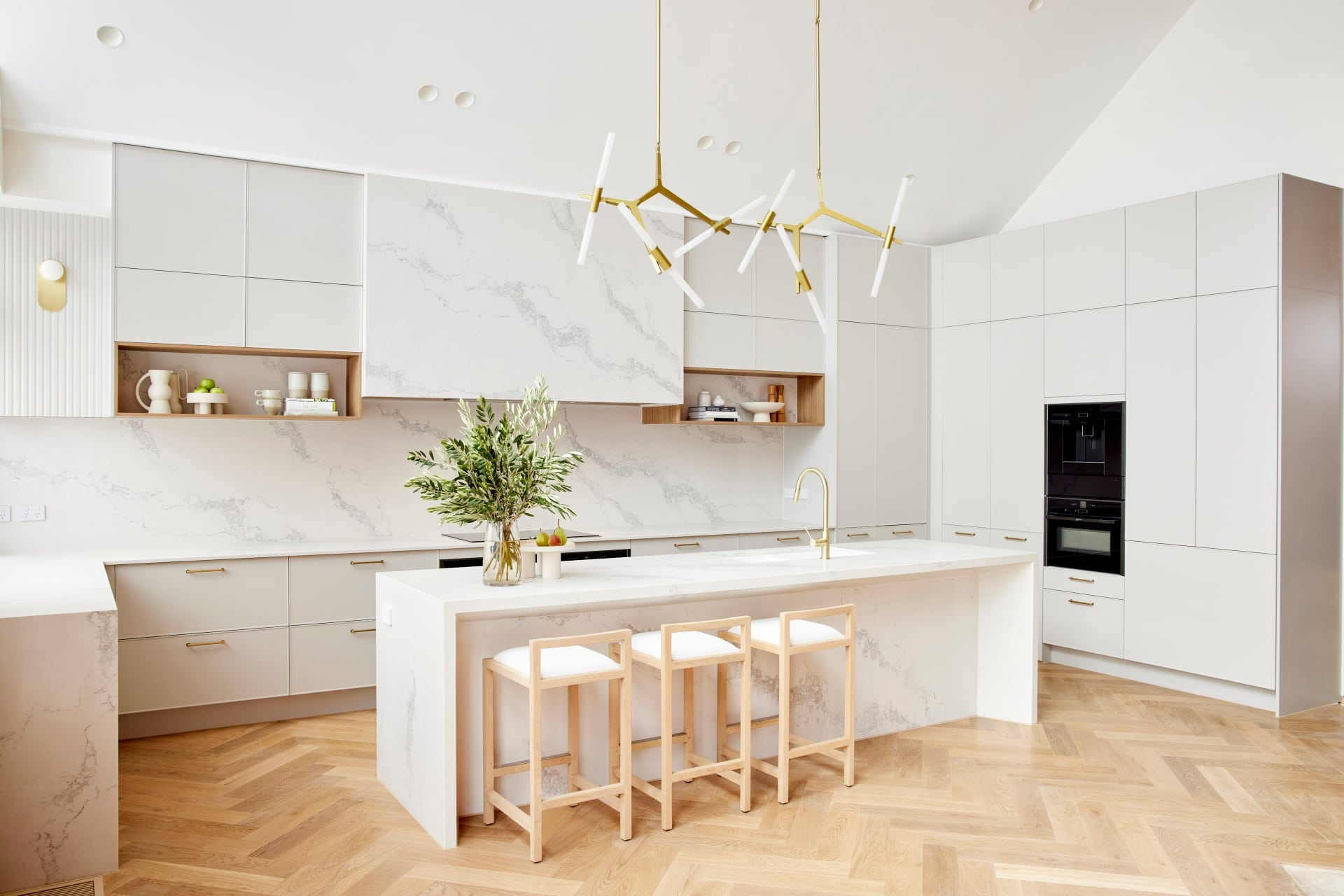 the block 2021 ronnie and georgia kitchen with marble counterops light grey cabinets brass pendant lights