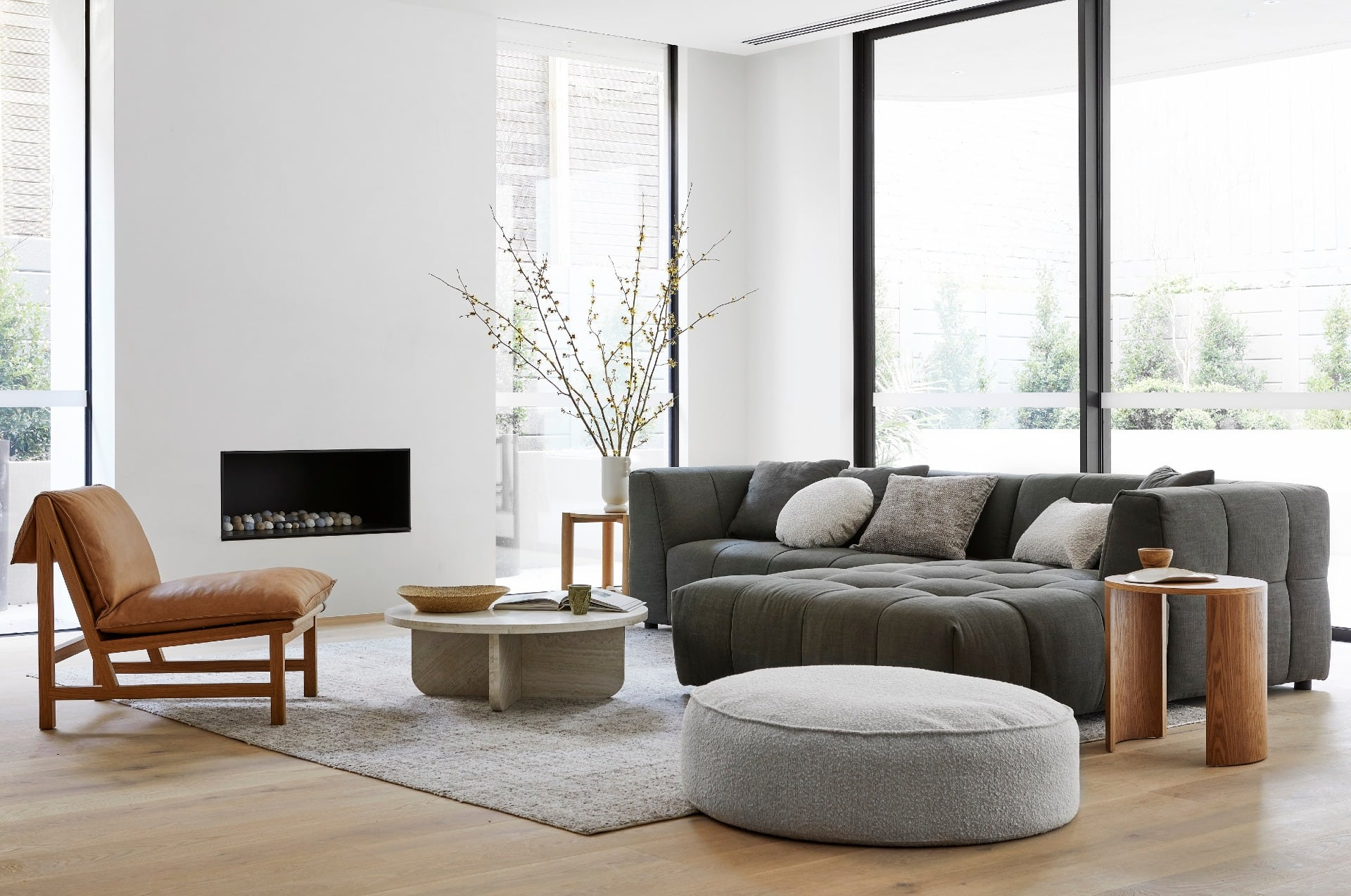 white and grey living room globewest with tan leather armchair and grey floor rug