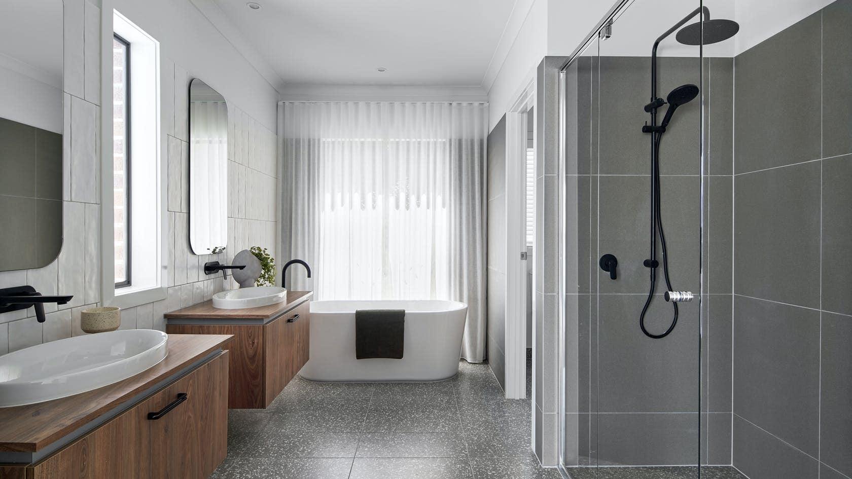 white sheer curtains on bathroom window behind freestanding bathtub