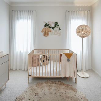 bohemian nursery with blonde timber crib and sheer curtains gender neutral colours