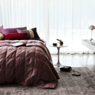 feminine bedroom with deep pink quilt cover and polished concrete flooring
